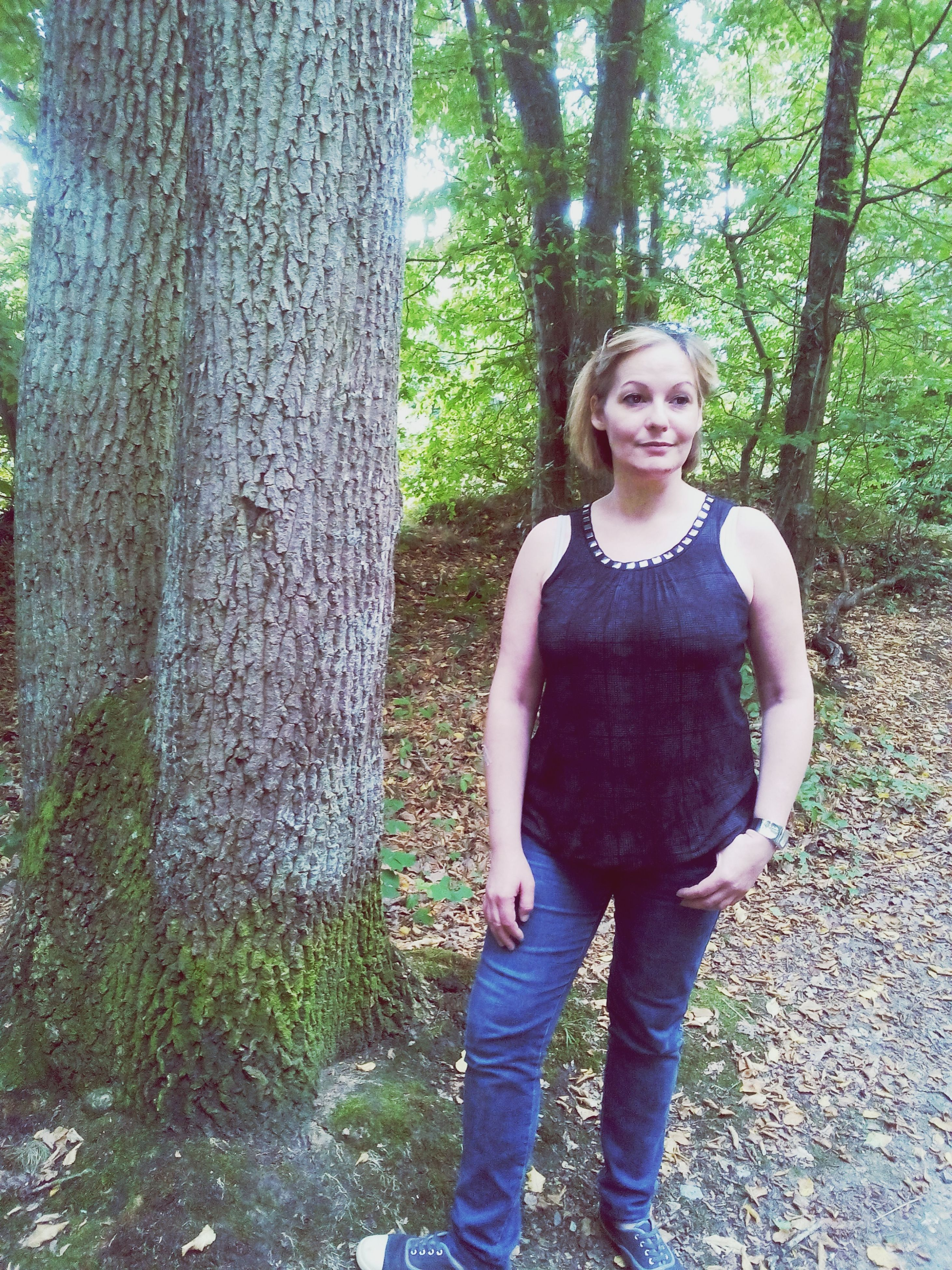 tree, person, lifestyles, casual clothing, standing, young adult, leisure activity, front view, looking at camera, portrait, tree trunk, young women, smiling, three quarter length, growth, full length, forest, happiness