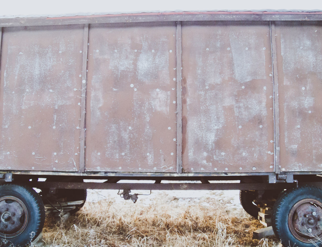 Side view of an old wagon standing in the field in winter. Cart Circus Covered Wagon Freight Transportation Obsolete Old Old-fashioned Outdoors Plank Retro Styled Rural Scene Transportation Travel Wagon  Wheels Wood