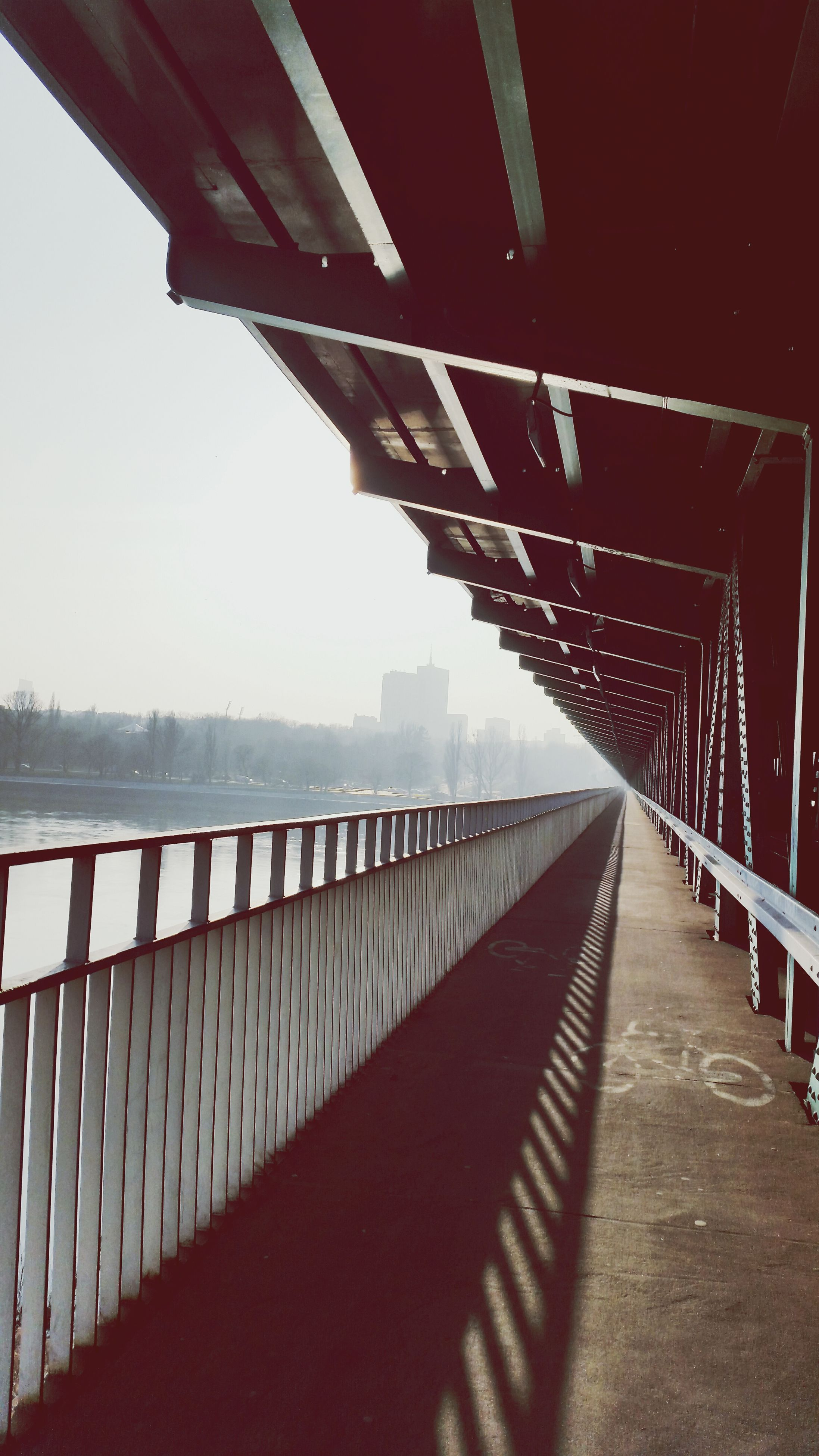 built structure, architecture, the way forward, railing, bridge - man made structure, diminishing perspective, connection, vanishing point, bridge, long, sky, water, building exterior, footbridge, city, transportation, river, outdoors, no people, clear sky