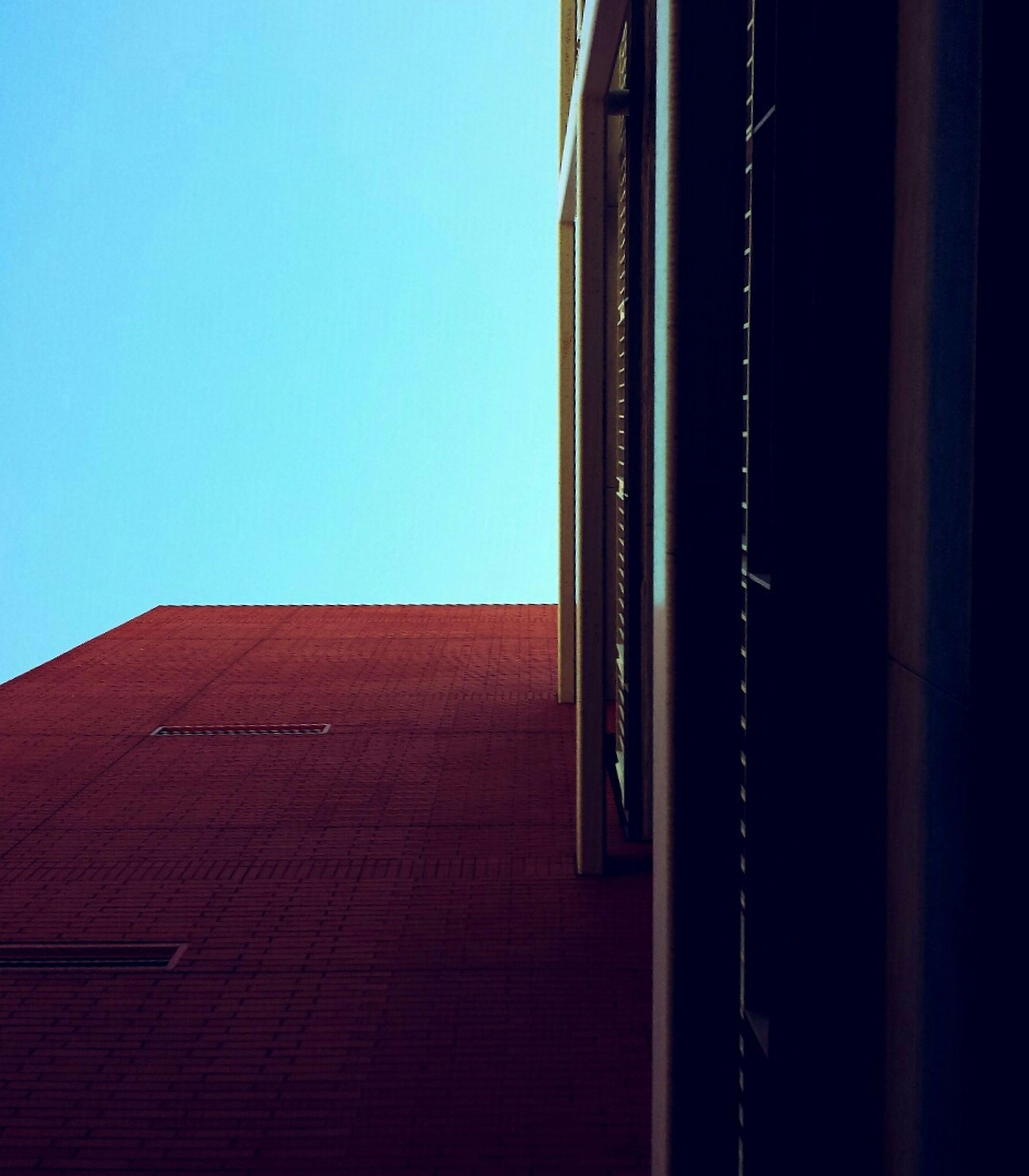 architecture, built structure, building exterior, low angle view, clear sky, building, window, city, copy space, outdoors, no people, day, residential structure, blue, brick wall, residential building, sky, high section, wall - building feature, exterior
