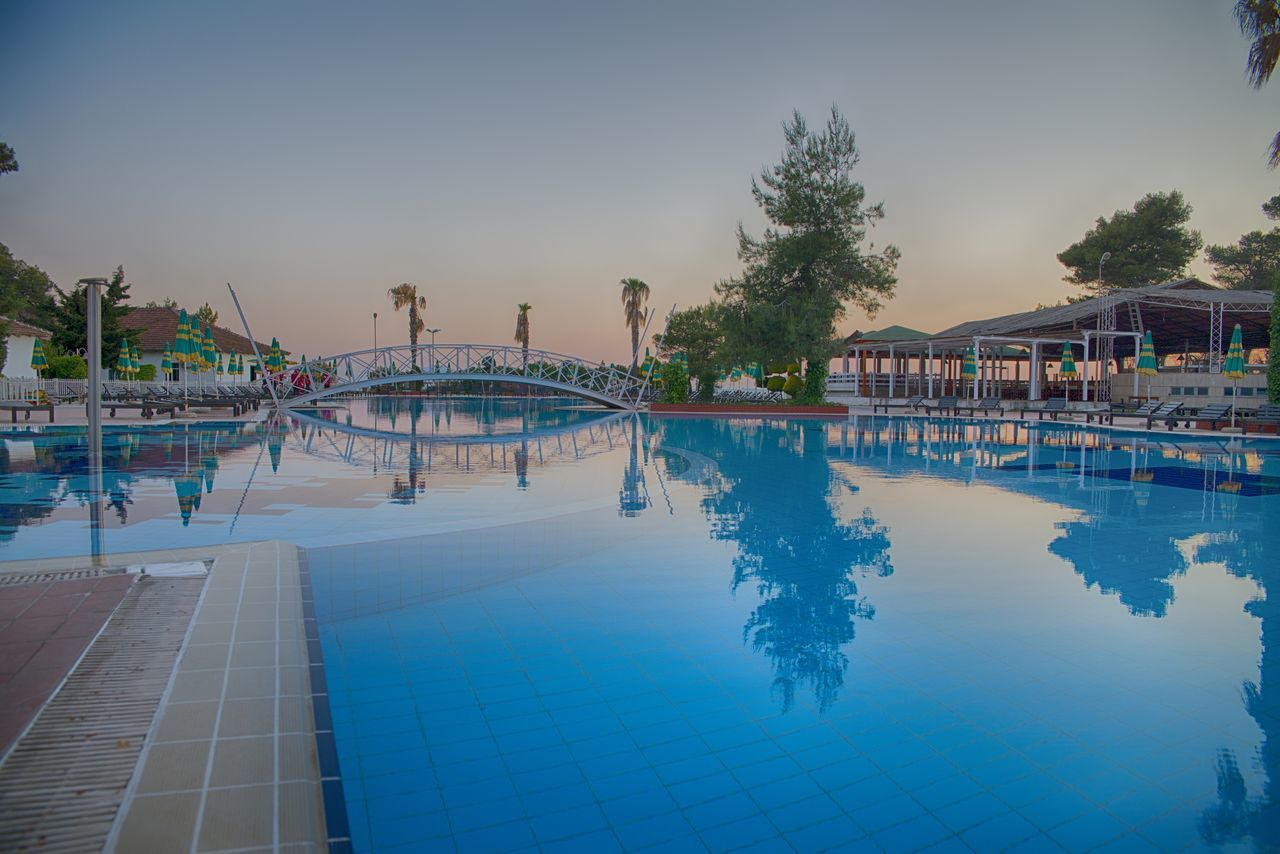 swimming pool, water, architecture, built structure, outdoors, building exterior, vacations, tourist resort, tree, sky, day, no people, clear sky, nature