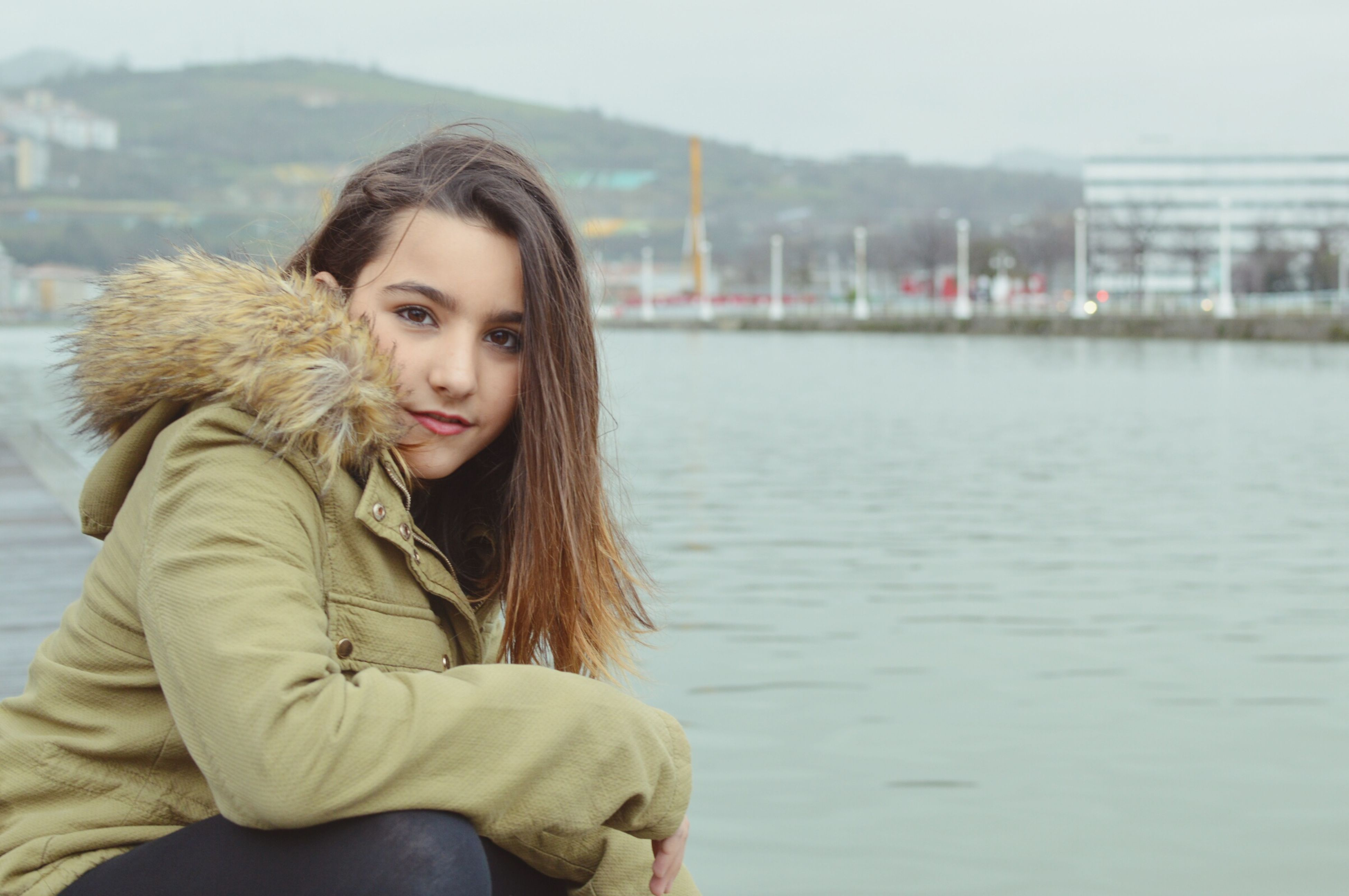 young adult, person, water, lifestyles, leisure activity, long hair, young women, waist up, casual clothing, focus on foreground, three quarter length, smiling, lake, brown hair, blond hair, river, standing, portrait