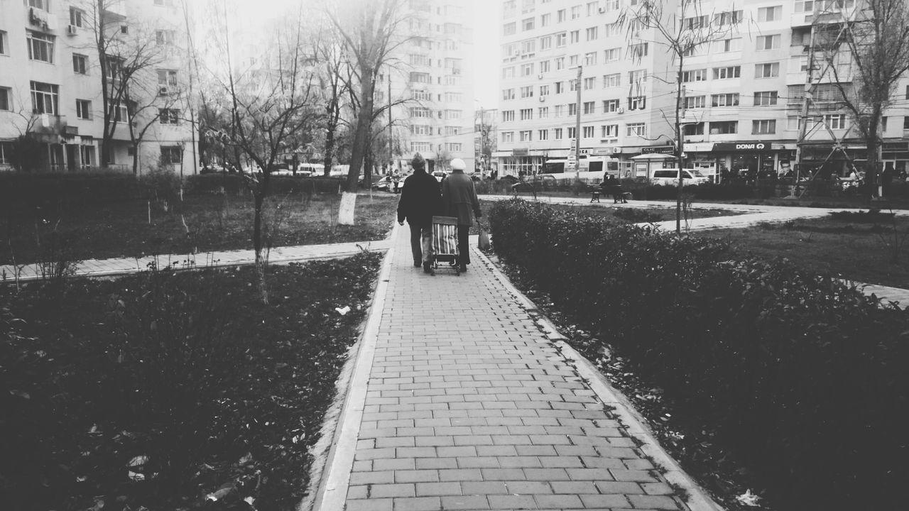 Rear View Of People Walking On Footpath Against Buildings