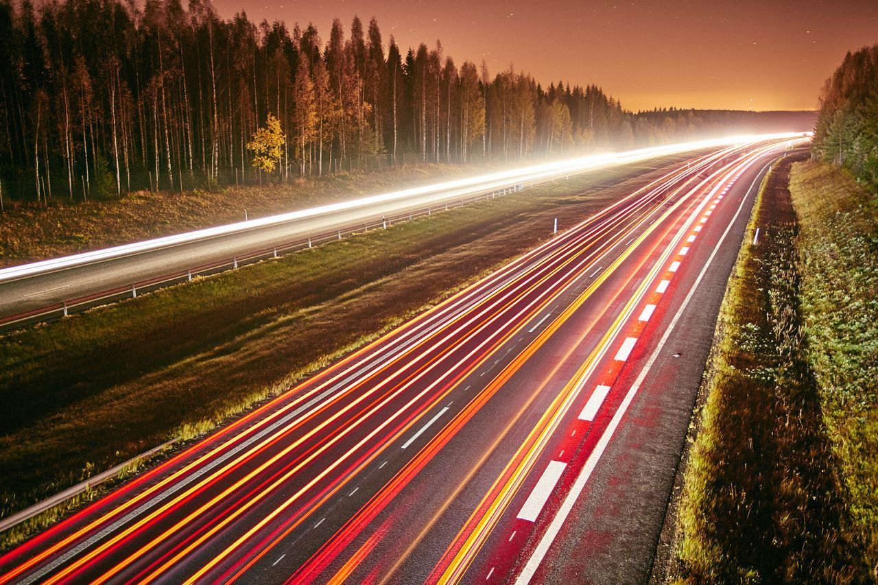Light trails of cars on a highway at night. Long exposure of fast moving traffic on a starry night. Blurred Motion Dramatic Fast Lane Heavy Traffic Highway Illuminated Lane Light Trail Light Trails Long Exposure Motion Movement Nature Night No People Outdoors Road Sky Speed Speeding Street Traffic Transportation Tree Velocity