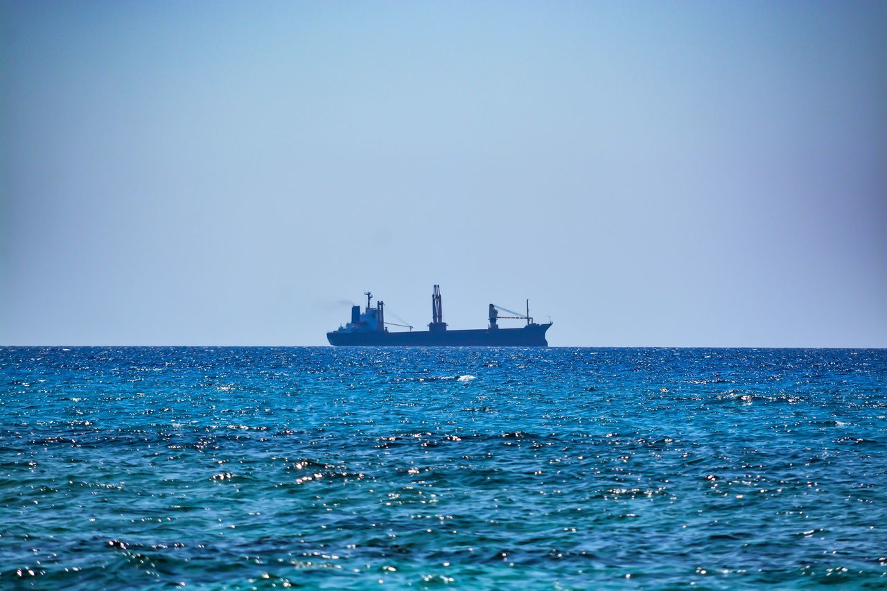 sea, water, horizon over water, clear sky, blue, copy space, nautical vessel, lighthouse, tranquility, waterfront, nature, scenics, day, outdoors, transportation, sky, ship, tranquil scene, beauty in nature, no people, sailing, offshore platform, drilling rig