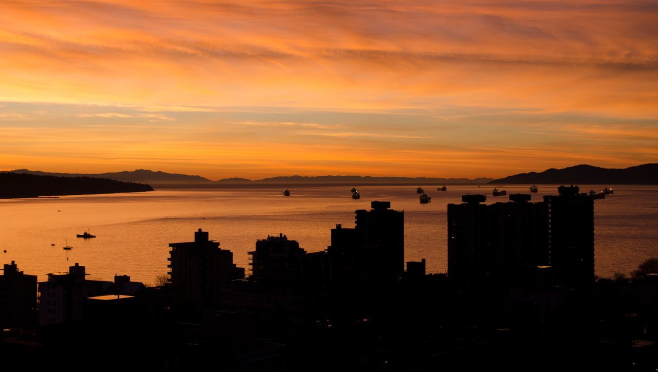sunset, architecture, orange color, building exterior, sea, silhouette, built structure, water, sky, nature, beauty in nature, cityscape, scenics, no people, outdoors, city, travel destinations, cloud - sky, skyscraper, horizon over water