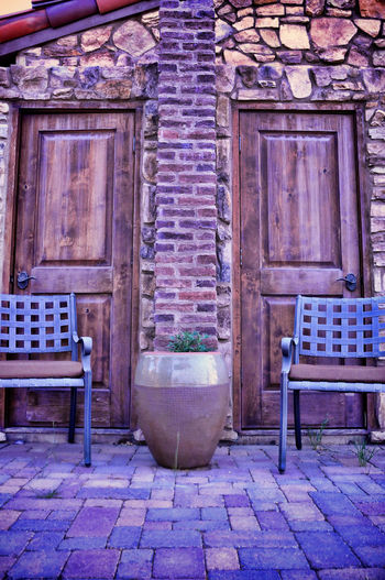 Tuscany Rustic Doors on porch Brick Wall Rustic Doors Tuscany Home Architecture Barrel Brick Building Exterior Built Structure Chair Cottage Life Day Home Renovation  No People Outdoors Patio Furniture Pavement Patterns Paver Walkway Seat