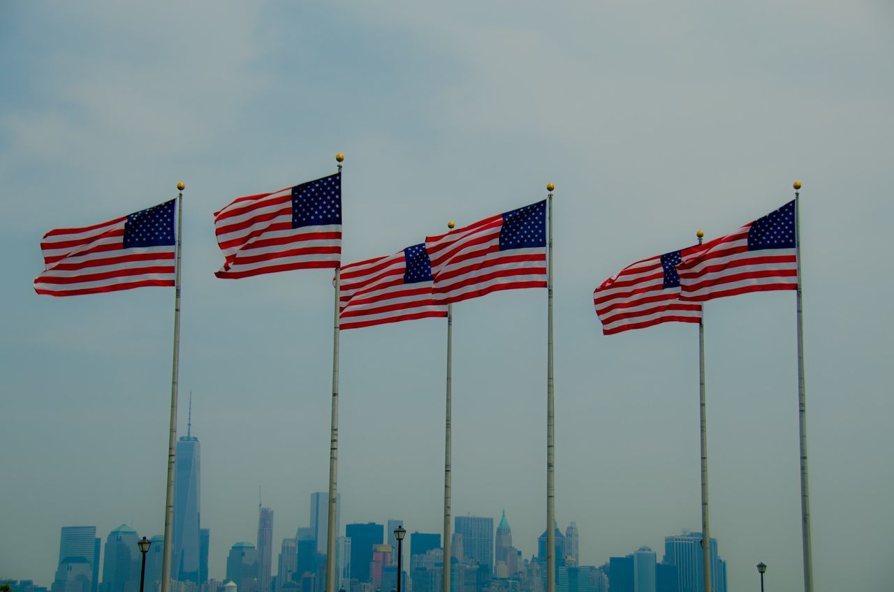 Low angle view of American flags in front of cityscape against cloudy sky