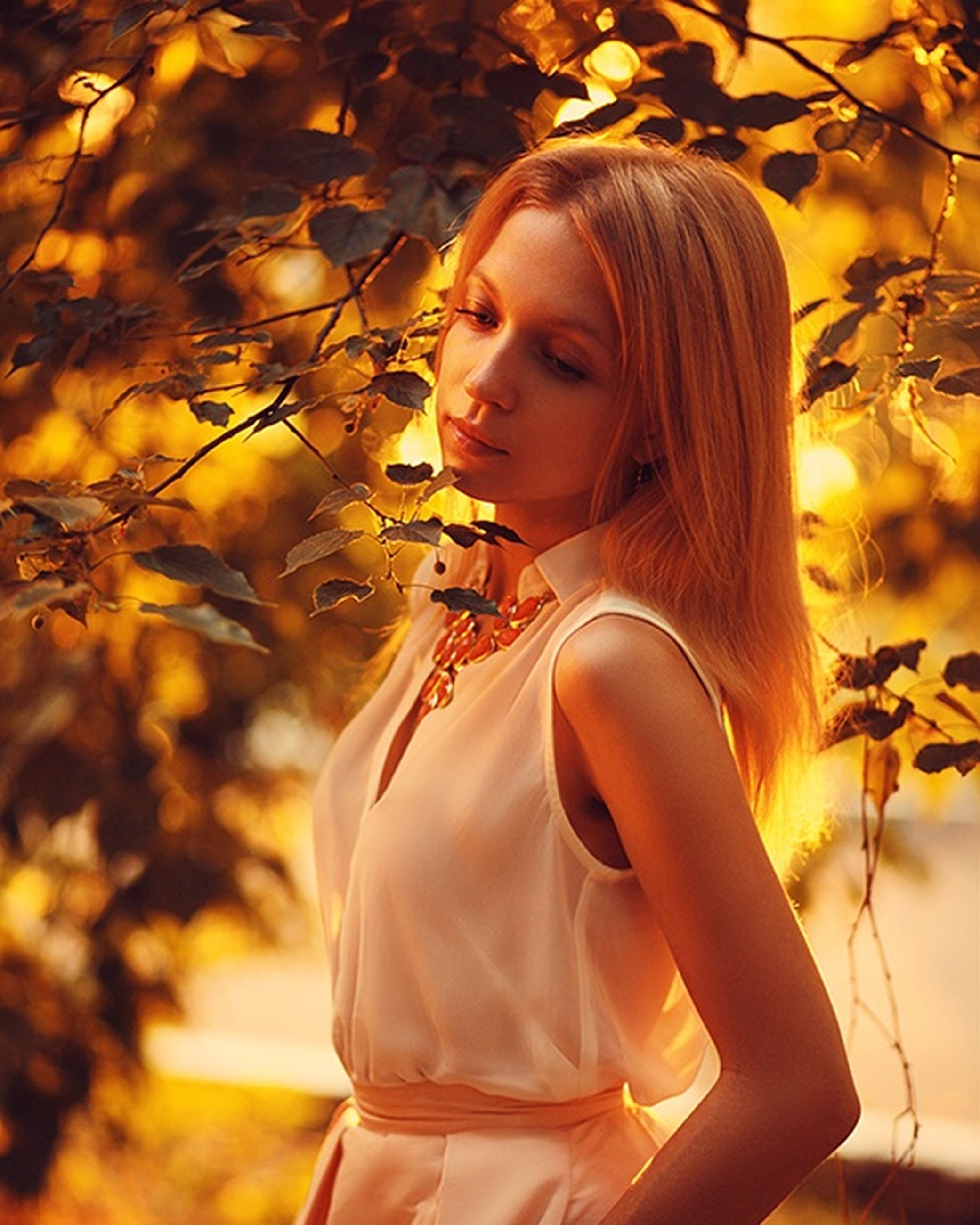 person, lifestyles, young adult, young women, casual clothing, leisure activity, standing, flower, long hair, portrait, front view, three quarter length, looking at camera, tree, focus on foreground, plant