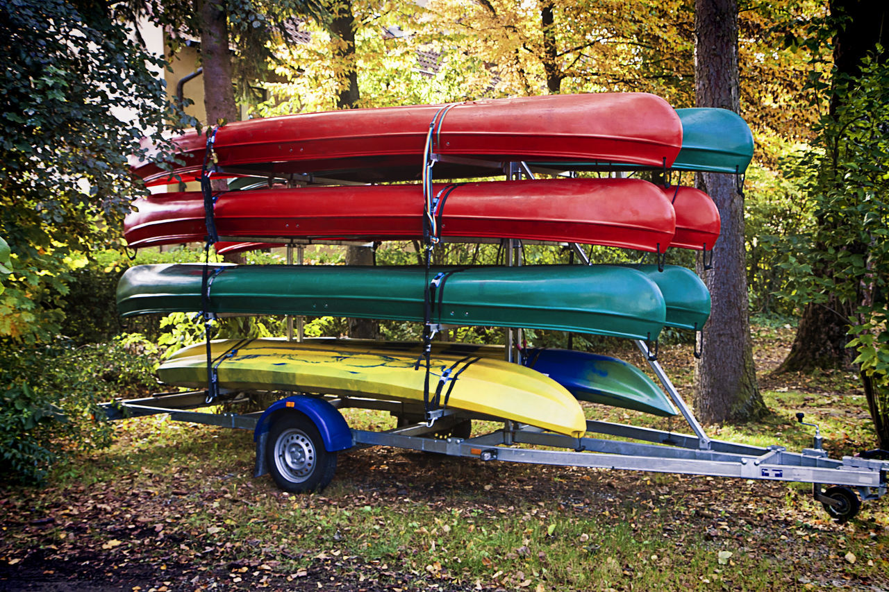 Colorful canoes arranged in racks stored on a parked car trailer Boats Canoes Colorful Day Hobby Kayak Leisure Activity Multi Colored No People Outdoors Parked Rack Red Roadside Rowing Boats Storage Summer Summer ☀ Trailer Transportation Travel Tree Vacations Water Sports