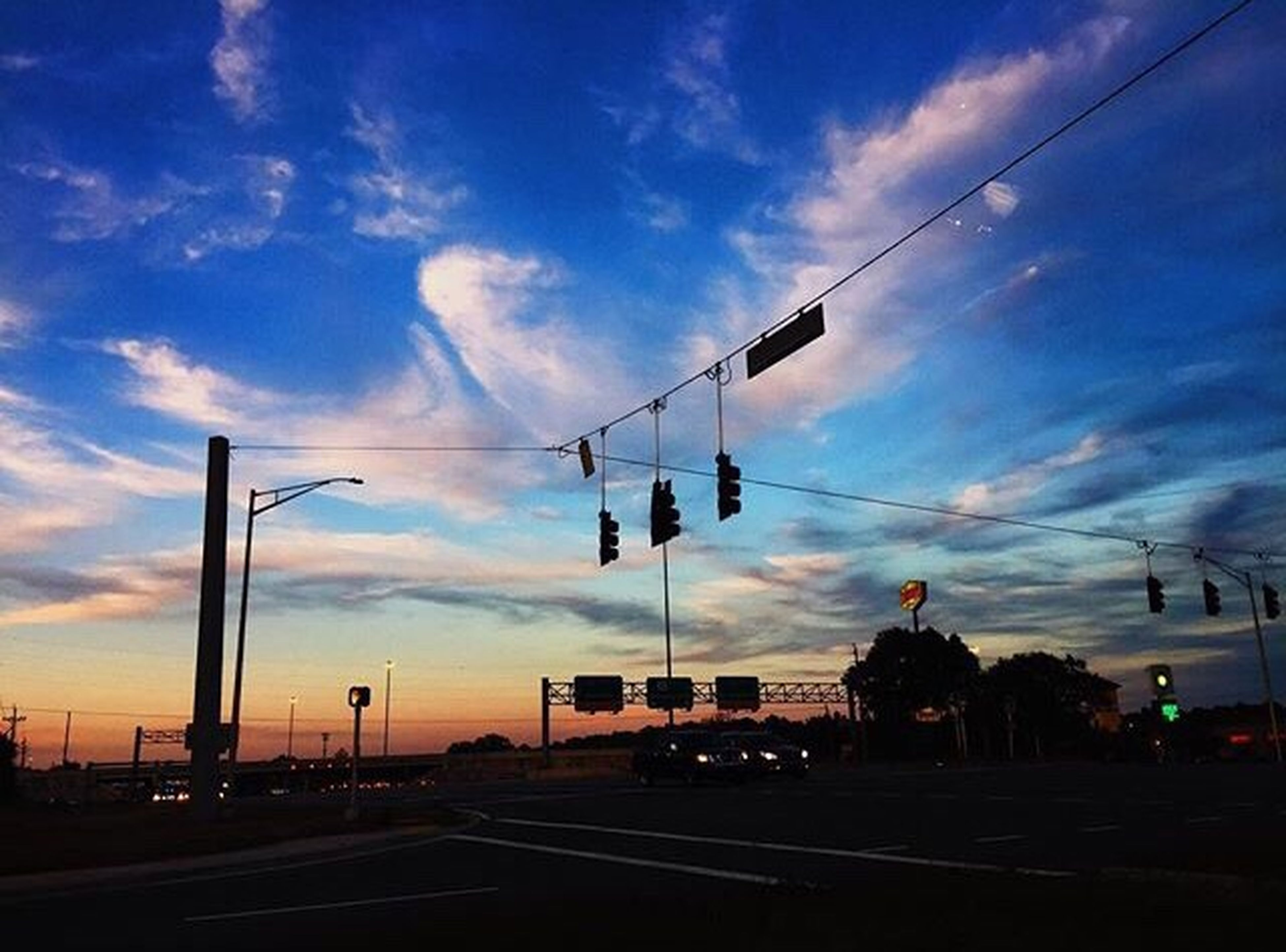 cloud - sky, sky, transportation, cable, car, stoplight, road, built structure, sunset, architecture, building exterior, silhouette, outdoors, city, street light, road sign, day, no people, telephone line