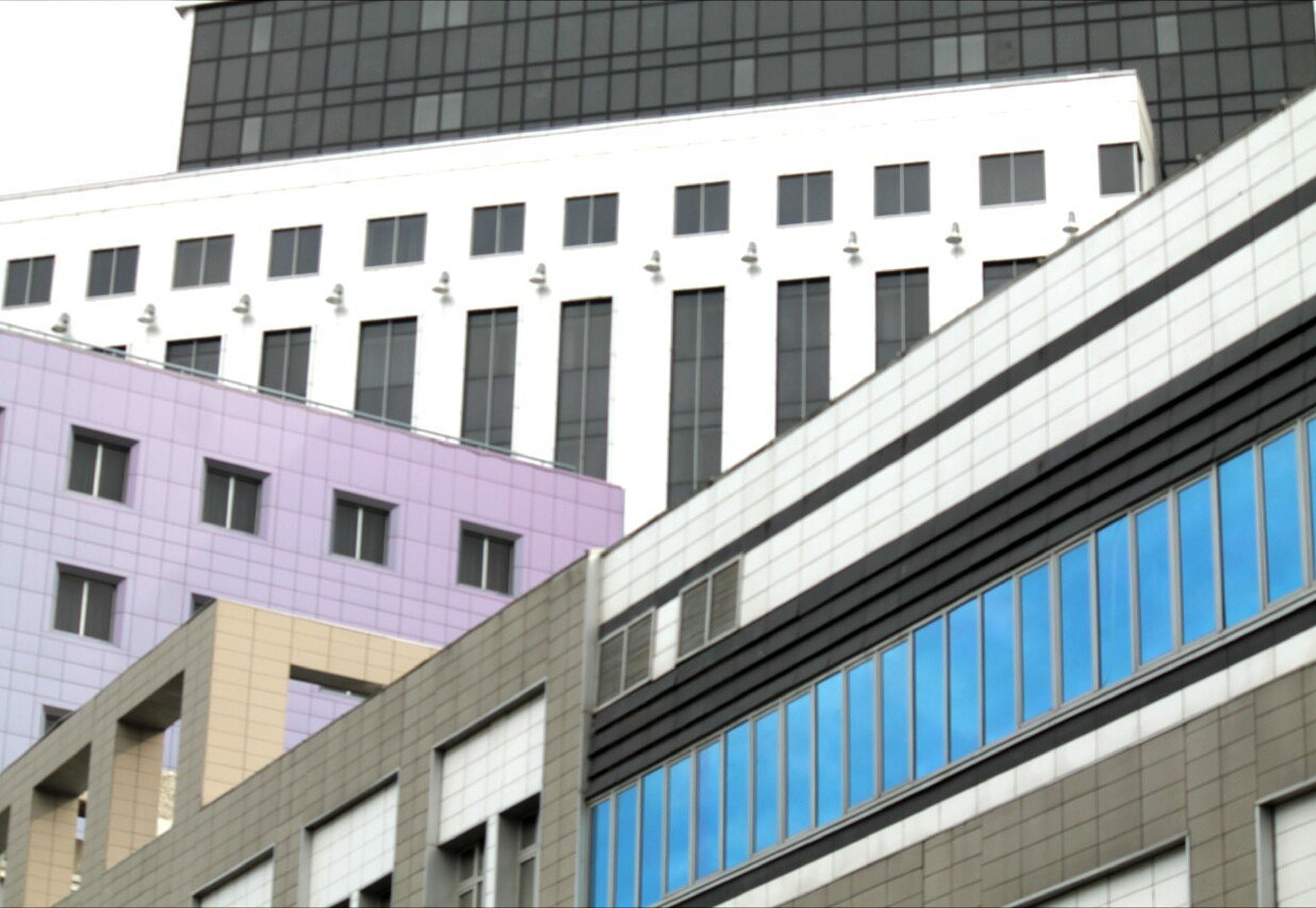 building exterior, architecture, built structure, low angle view, window, city, modern, office building, building, repetition, skyscraper, tower, building story, architectural feature, city life, tall - high, day, outdoors, development, full frame, office block, facade, no people, geometric shape