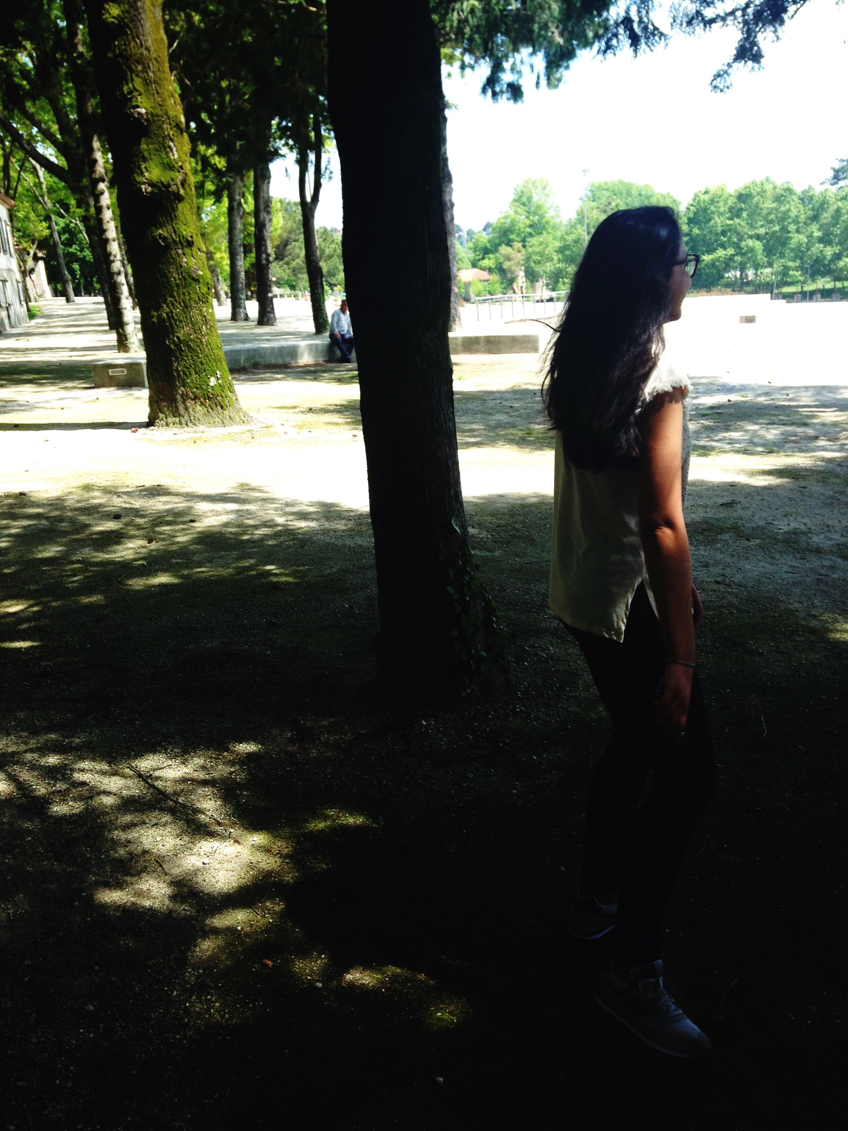 tree, lifestyles, leisure activity, casual clothing, person, full length, tree trunk, standing, childhood, sunlight, side view, young adult, park - man made space, day, growth, rear view, shadow