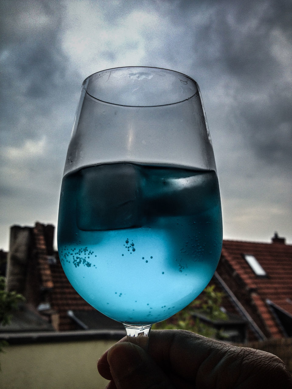 human hand, sky, human body part, holding, drink, real people, one person, close-up, cloud - sky, drinking glass, food and drink, personal perspective, refreshment, alcoholic drink, human finger, alcohol, focus on foreground, outdoors, day, building exterior, wineglass, architecture, freshness, people