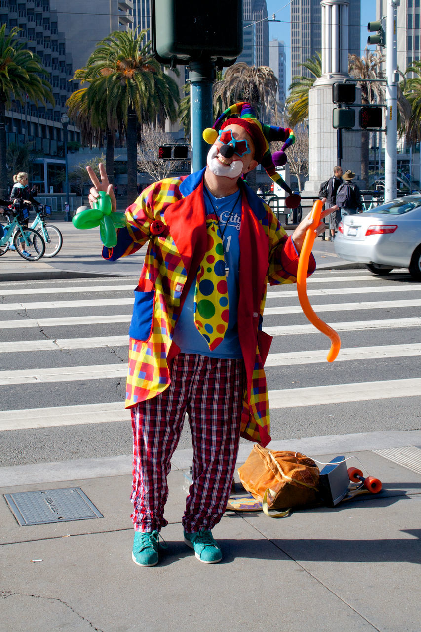 street, one person, building exterior, outdoors, costume, city street, day, city, real people, full length, front view, architecture, standing, clown, holding, built structure, multi colored, one man only, young adult, adult, people, adults only