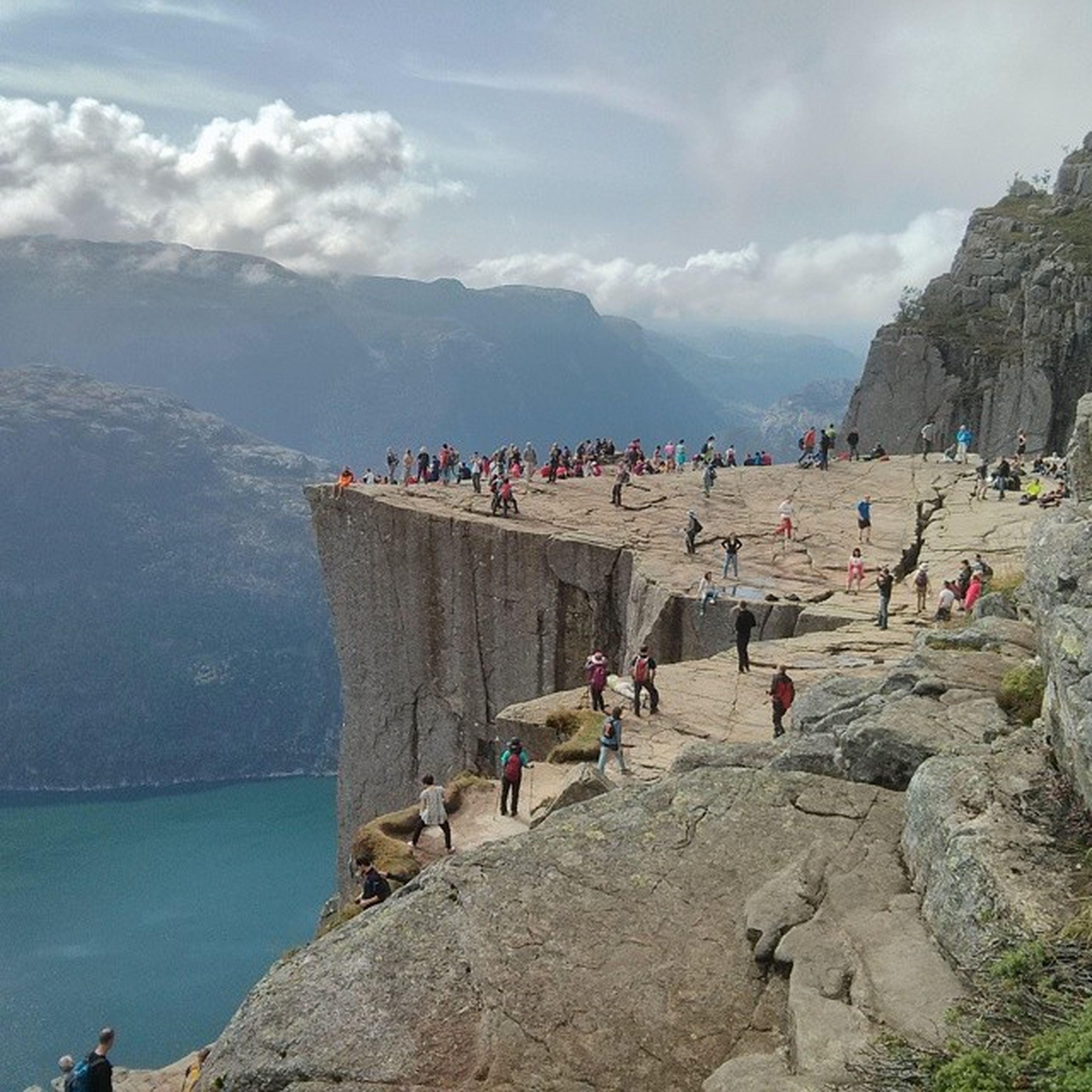 large group of people, sky, water, mountain, men, person, tourist, lifestyles, sea, leisure activity, rock - object, vacations, beach, cloud - sky, tourism, mixed age range, built structure, medium group of people, nature