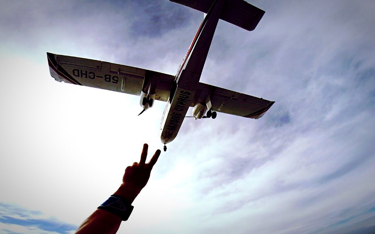 sky, flying, human hand, one person, low angle view, outdoors, airplane, real people, day, human body part, people