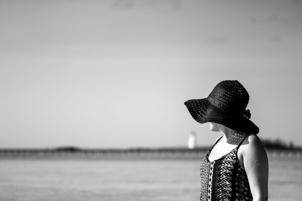 sea, hat, real people, one person, side view, focus on foreground, water, sun hat, sky, outdoors, standing, beach, lifestyles, day, women, young women, young adult, nature, people