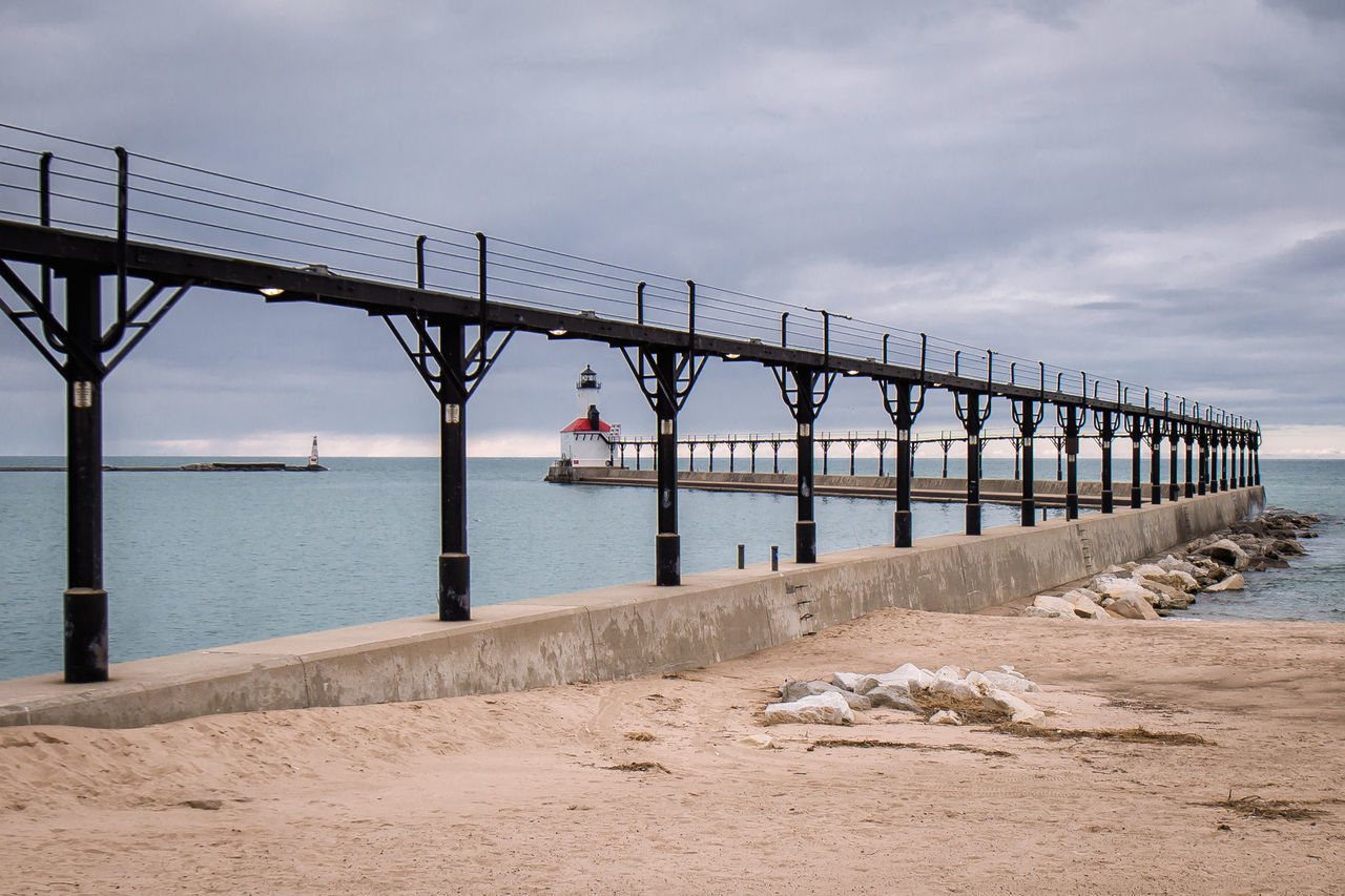 Bridge - Man Made Structure Beach Connection Horizon Over Water Water Outdoors Sand Landscape Sky No People Beauty In Nature Nature Day Lake Michigan Indiana Dunes Lakeshore Indiana Dunes Travel Destinations Tourism Leisure Activity Scenics Lighthouse Lighthouseview Waterfront Lake Lakeshore
