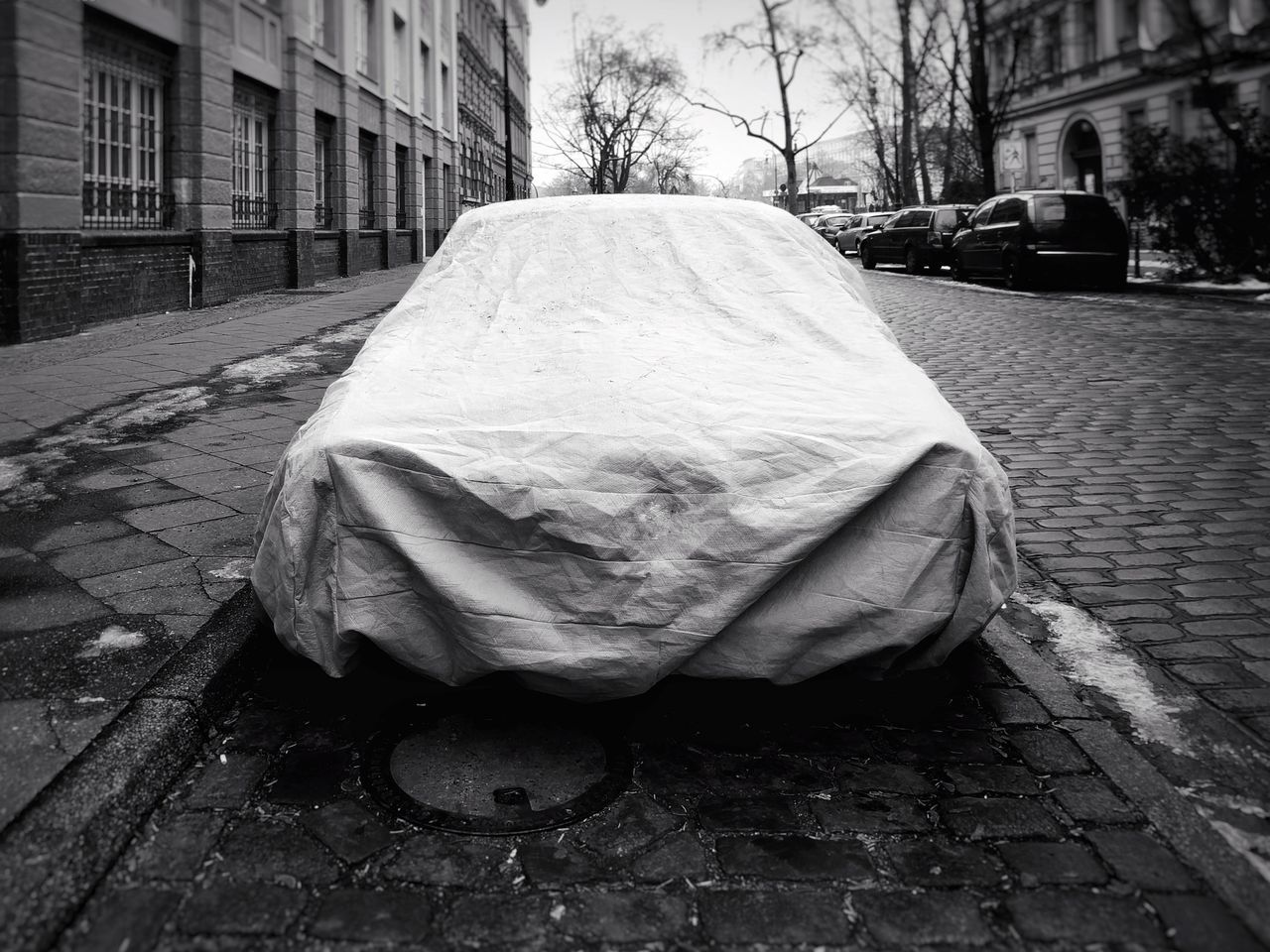 I Got You Covered . Building Exterior Architecture Built Structure City No People Day Outdoors Protecting Protection Black And White Vintage Cars Cover Covering Covered Wintertime Front View Artistic Secrets Car City Architecture Softgarage Car Show Streetportrait