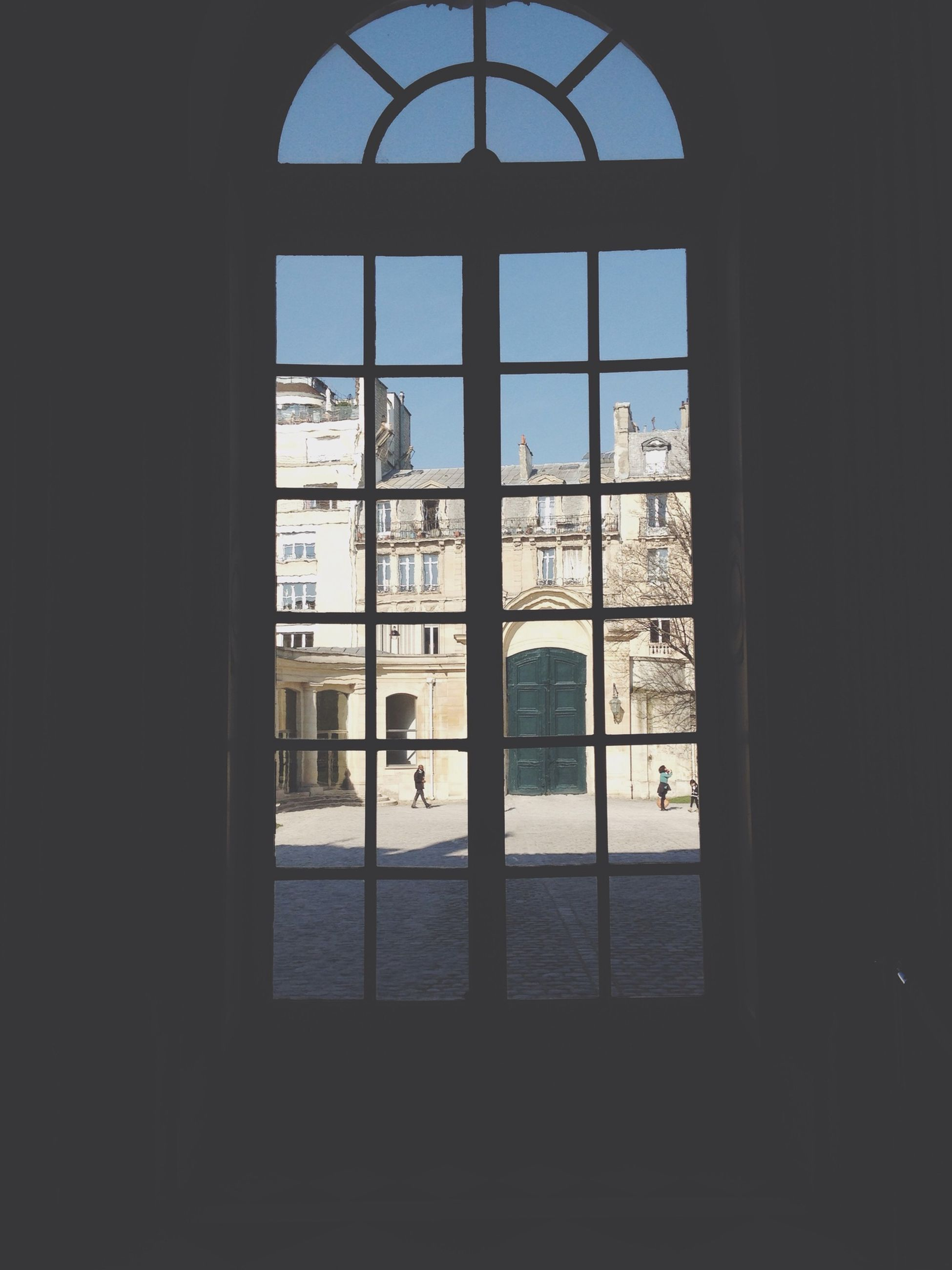indoors, window, architecture, built structure, glass - material, building exterior, transparent, arch, city, building, day, sunlight, interior, dark, sky, clear sky, reflection, entrance, silhouette, door