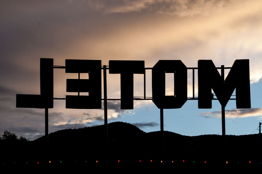 Reverse Motel Sign Back To Front Beauty In Nature Black Color Cloud Cloud - Sky Information Information Sign Letters Motel Motel Sign No People Outdoors Reverse Road Trip Scenics Sign Silhouette Sky Sunset Text Type Western Script Feel The Journey