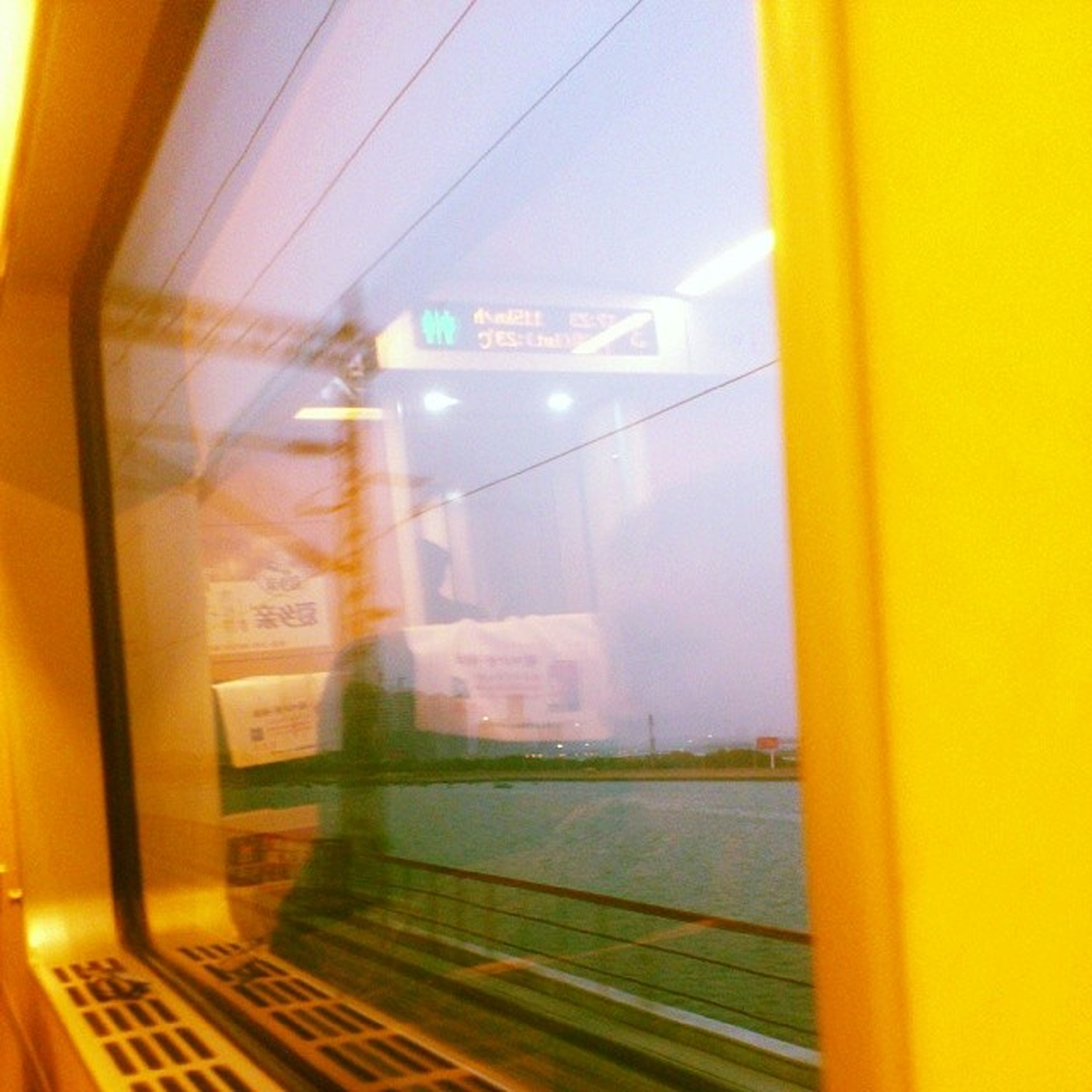 transportation, glass - material, window, transparent, indoors, vehicle interior, public transportation, mode of transport, travel, yellow, train - vehicle, journey, reflection, rail transportation, built structure, on the move, communication, architecture, land vehicle, train