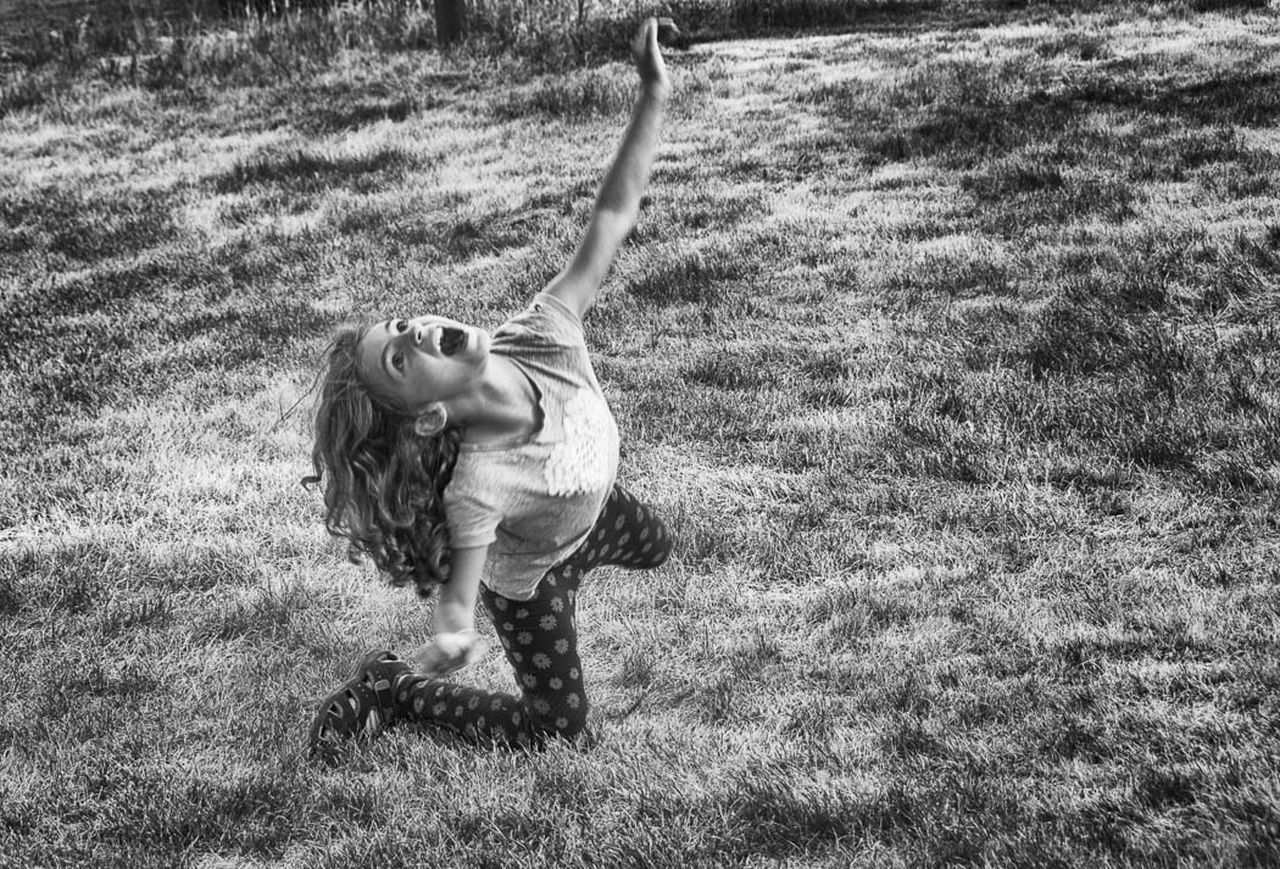 grass, childhood, field, one person, arms raised, happiness, fun, nature, casual clothing, outdoors, day, full length, real people, elementary age, leisure activity, lifestyles, smiling, children only, people