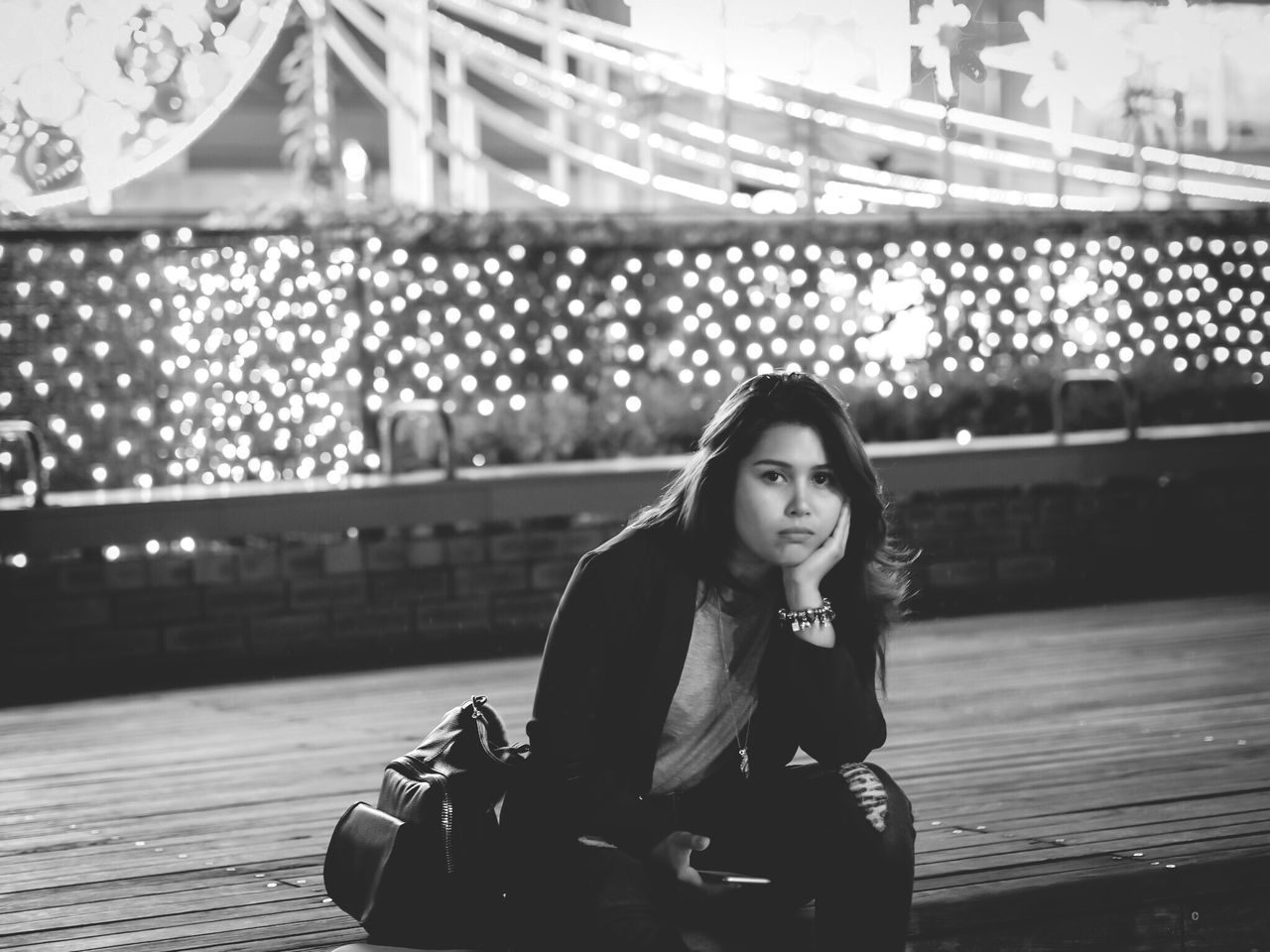 real people, young adult, one person, young women, lifestyles, sitting, focus on foreground, leisure activity, looking at camera, front view, bridge - man made structure, beautiful woman, portrait, outdoors, night, full length
