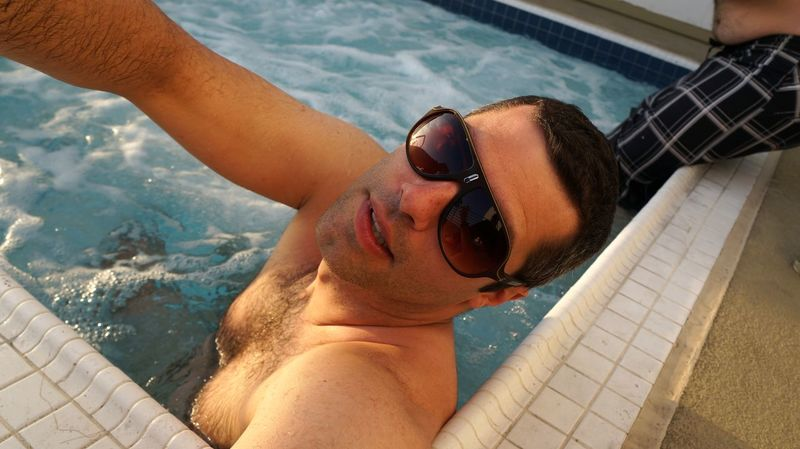 Front View Jacuzzi  Leisure Activity Lifestyles Looking At Camera Male Man Outdoors Person Portrait Real People Relaxation Shirtless Sitting Sunglasses Sunlight Vacations Water Young Adult