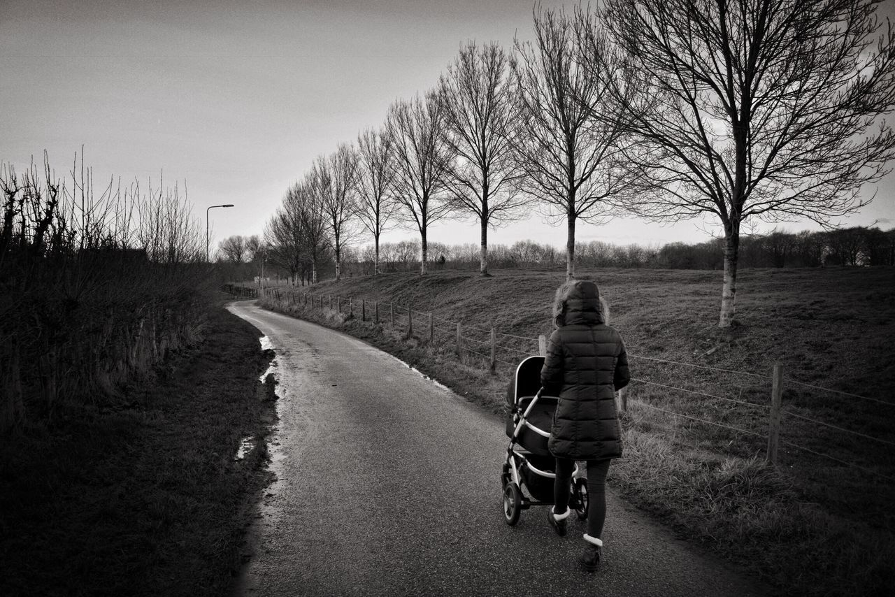 Rear View Of Woman Walking With Baby Carriage On Street