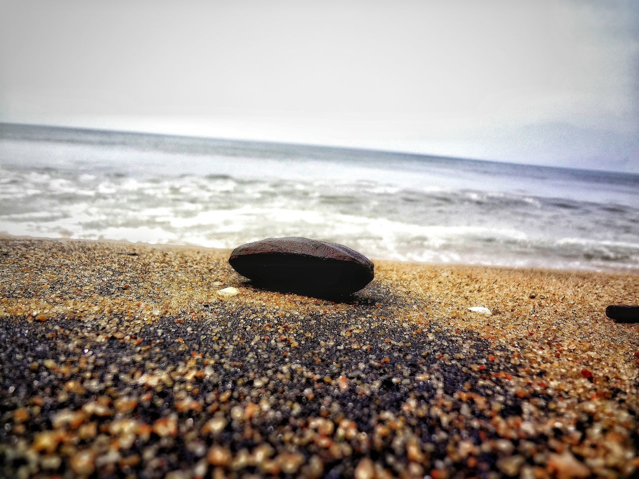 beach, sea, sand, shore, horizon over water, water, nature, tranquil scene, surface level, pebble, day, outdoors, tranquility, no people, scenics, beauty in nature, seashell, pebble beach, wave, close-up, sky