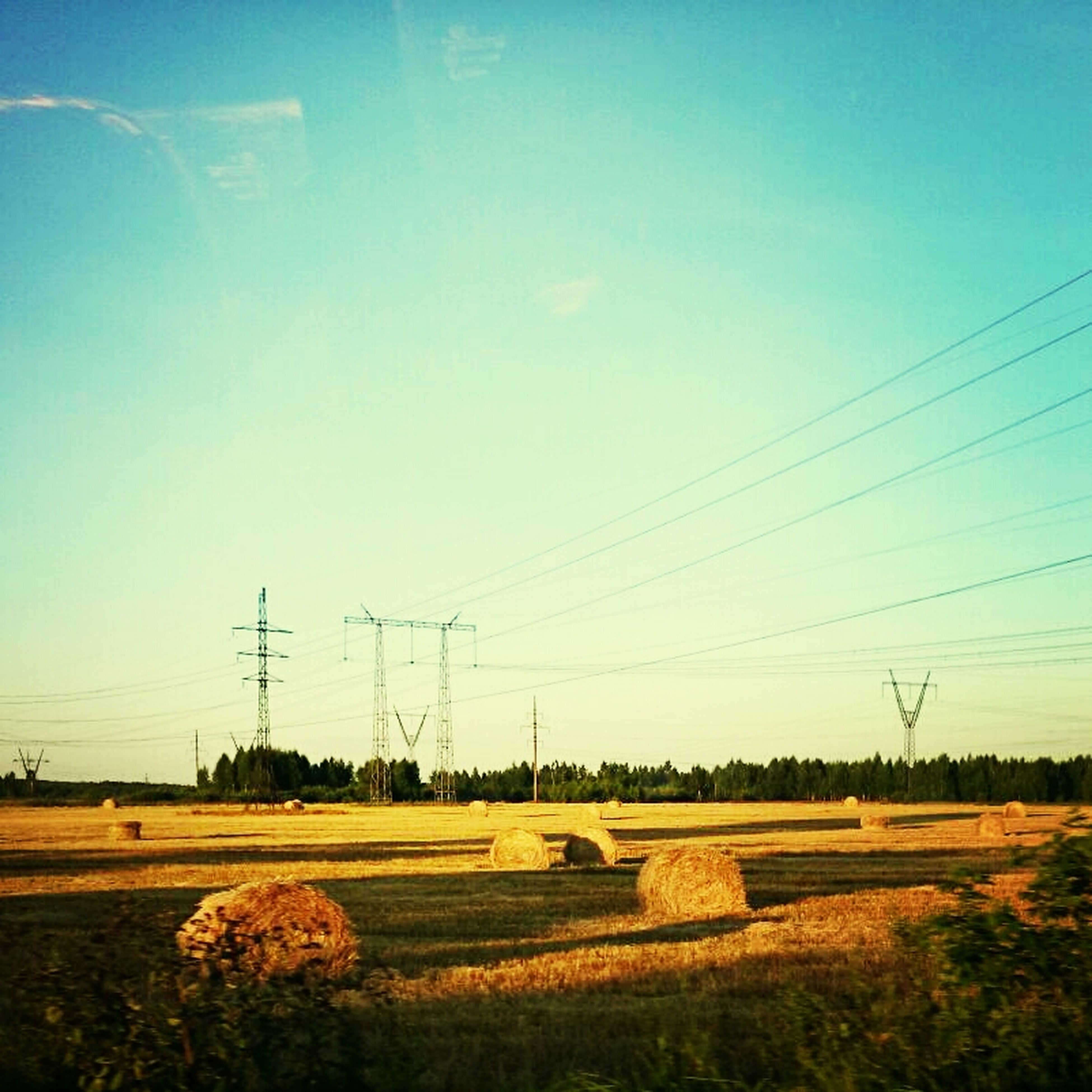power line, electricity pylon, power supply, fuel and power generation, electricity, field, landscape, rural scene, connection, cable, blue, clear sky, technology, agriculture, sky, farm, nature, tranquil scene, tranquility, grass