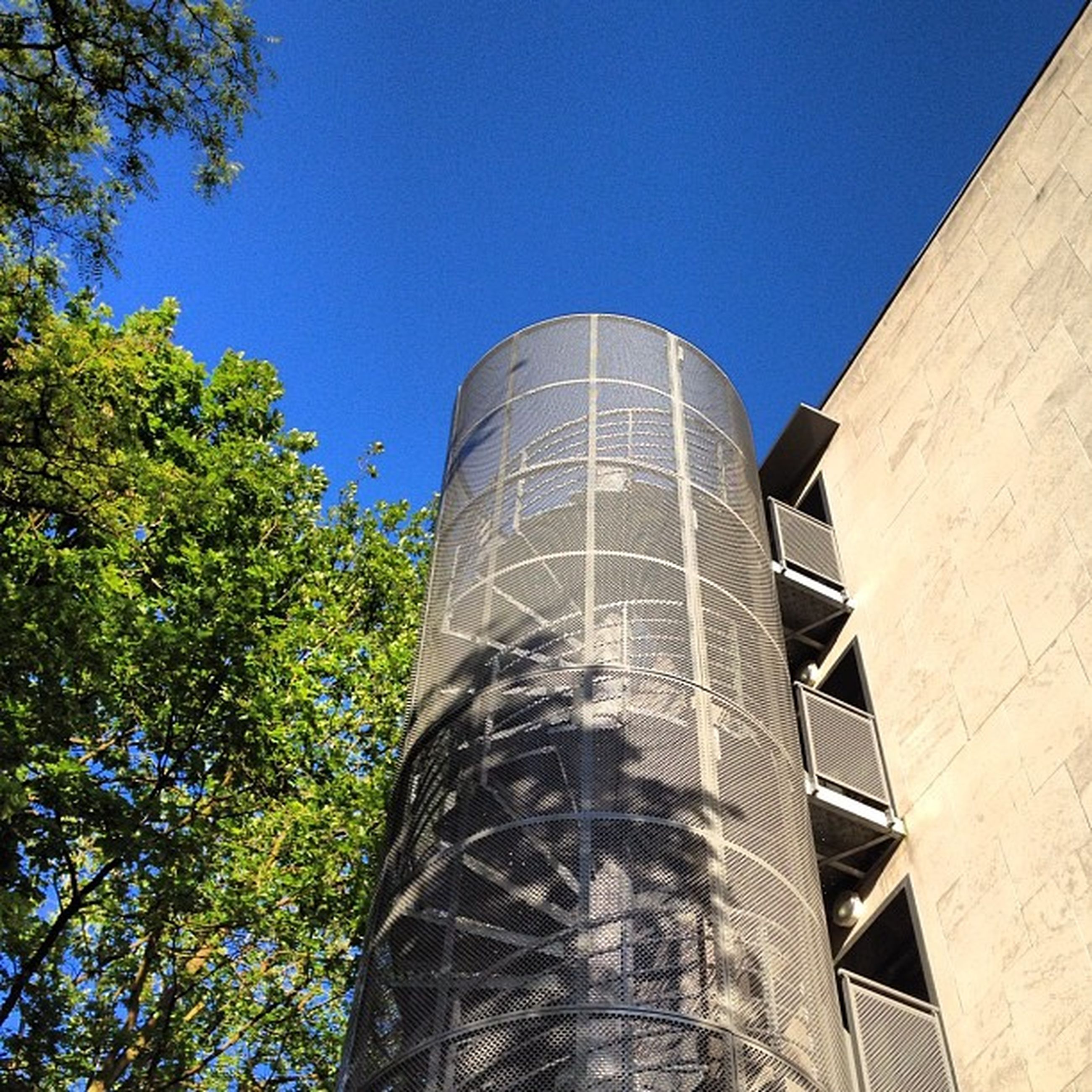 architecture, built structure, building exterior, clear sky, blue, low angle view, tree, tower, tall - high, famous place, copy space, modern, travel destinations, day, city, sunlight, outdoors, no people, building, architectural feature