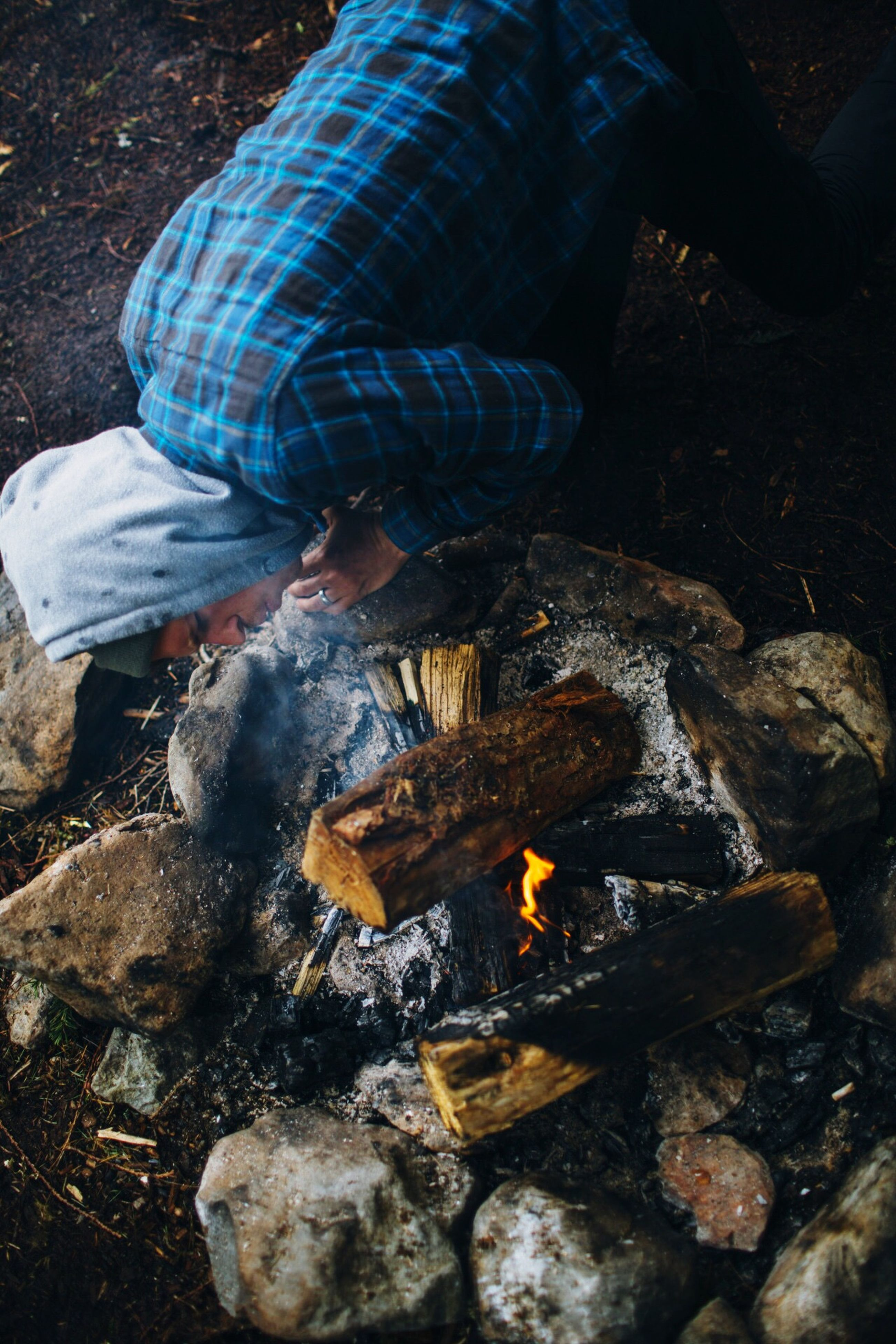 high angle view, rock - object, low section, fire - natural phenomenon, water, night, heat - temperature, outdoors, shoe, men, burning, stone - object, standing, flame, lifestyles, unrecognizable person, log, close-up