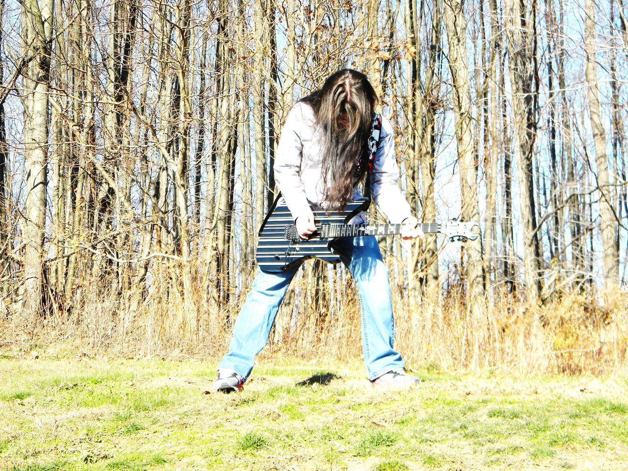 Guitar Guitarist Leisure Activity Long Hair Music Musical Instrument Musician One Person Real People Rock N Roll Tree Young Adult Young Men
