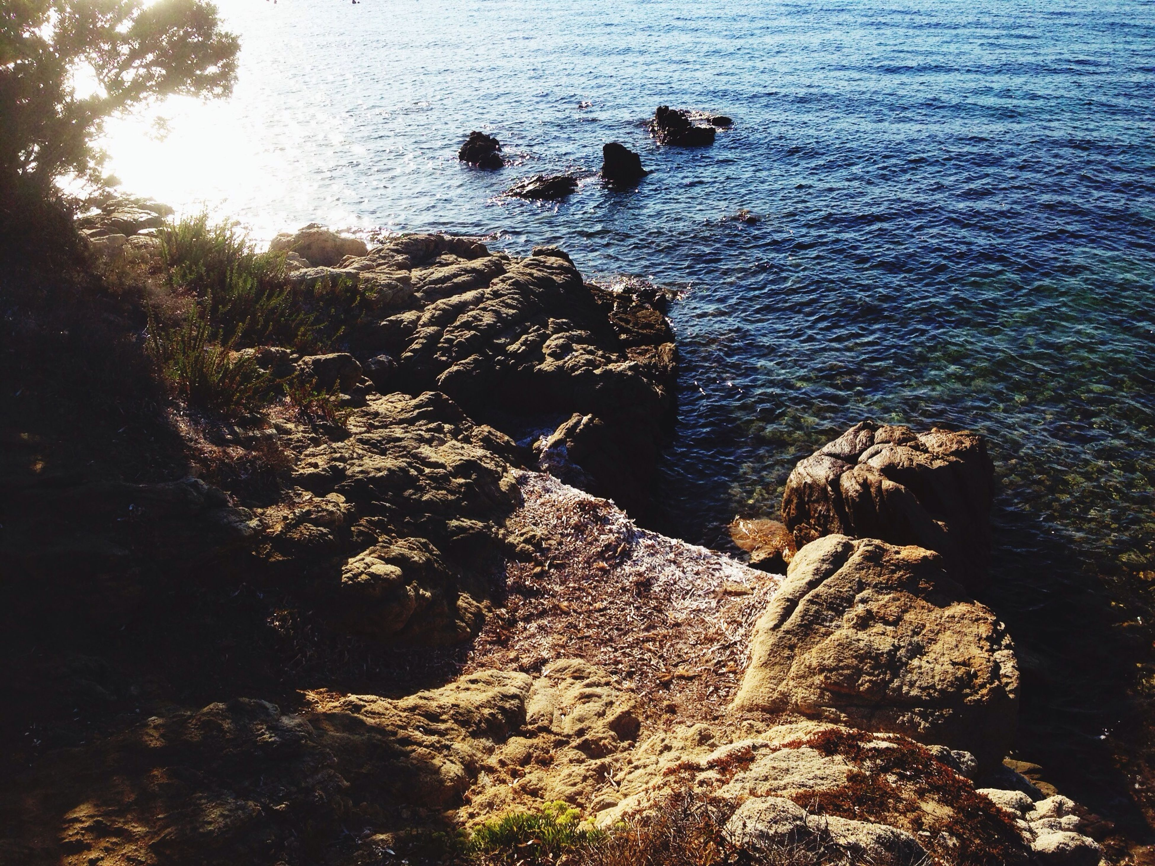 water, rock - object, high angle view, tranquility, rock formation, nature, tranquil scene, beauty in nature, scenics, sea, rock, sunlight, shore, idyllic, day, outdoors, no people, non-urban scene, beach, rippled