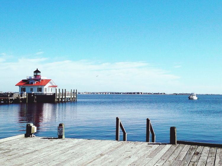Roanoke Marshes Lighthouse in Manteo, North Carolina. Water Lighthouse Outer Banks, NC Blue Boat