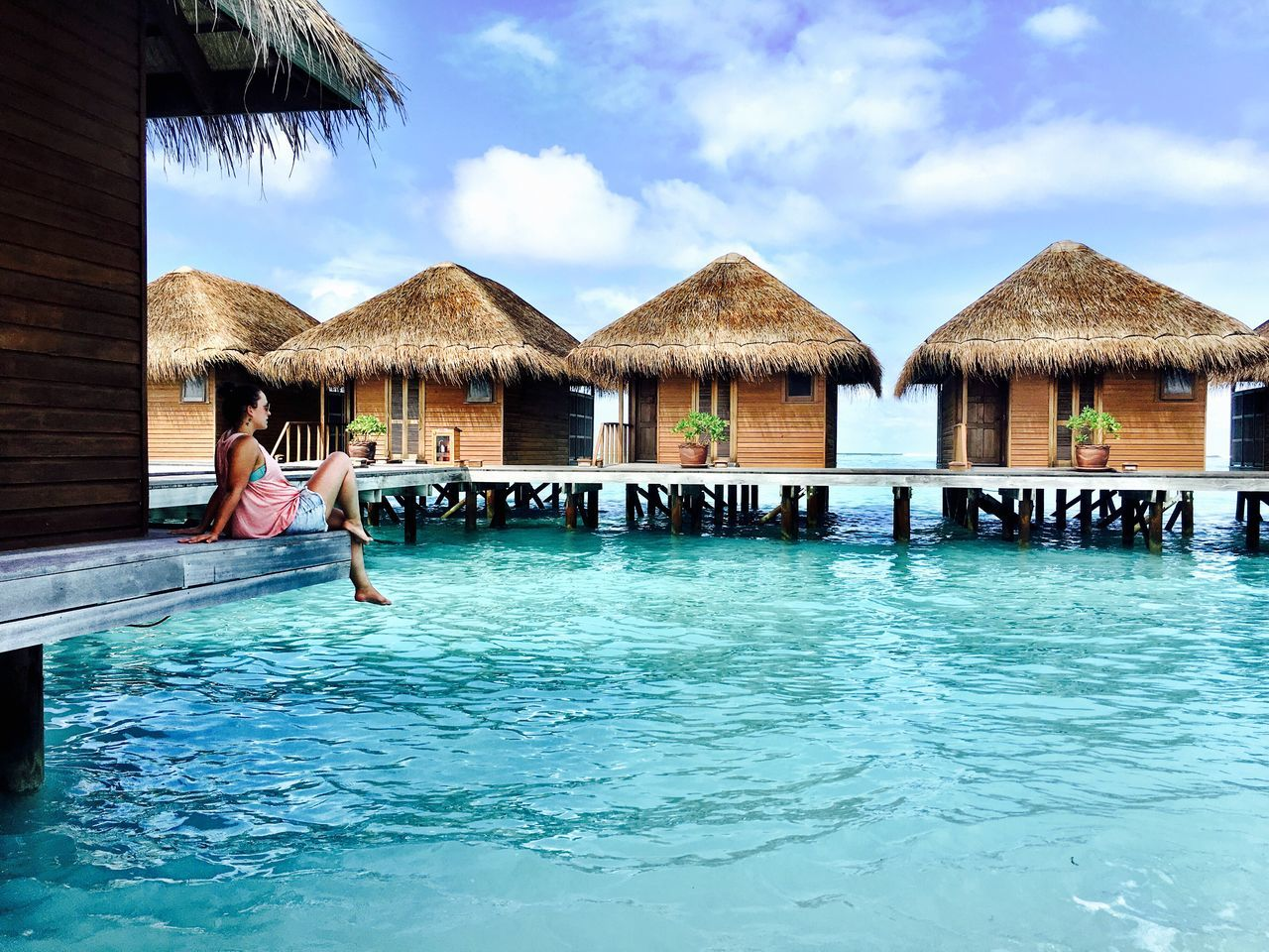 water, swimming pool, real people, thatched roof, sky, outdoors, day, sea, vacations, tourist resort, leisure activity, architecture, built structure, scenics, lifestyles, beauty in nature, one person, nature, holiday villa, people
