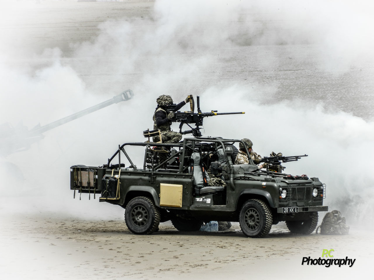 smoke - physical structure, real people, land vehicle, danger, day, military, men, outdoors, spraying, weapon, firefighter, army, fire engine
