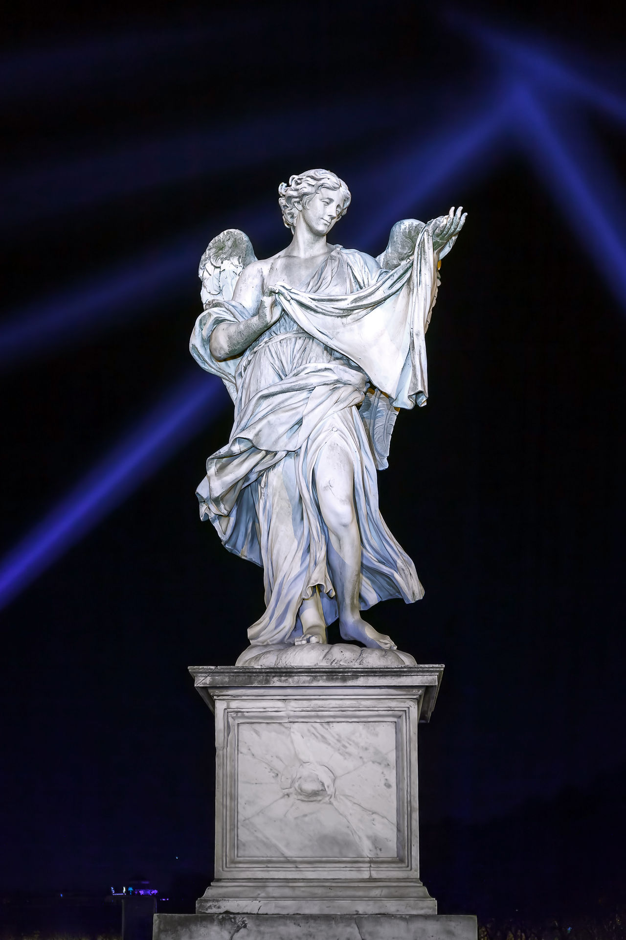 "Rome, Italy - January 1, 2017: Angel bearing Veronica's Veil by Cosimo Fancelli, with the inscription ""respice faciem Christi tui"" (""Look upon the face of your Christ"" Psalm 84:9), eastern side of the Ponte Sant'Angelo à Rome. Angel Angel Statue Architecture Black Background Blue Lights  Marble No People Sculpture Statue"