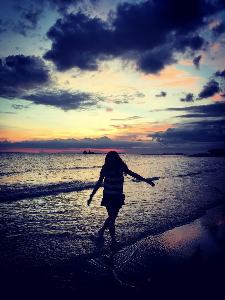 Rear View Of Girl Walking On Shore At Beach Against Sky During Sunset