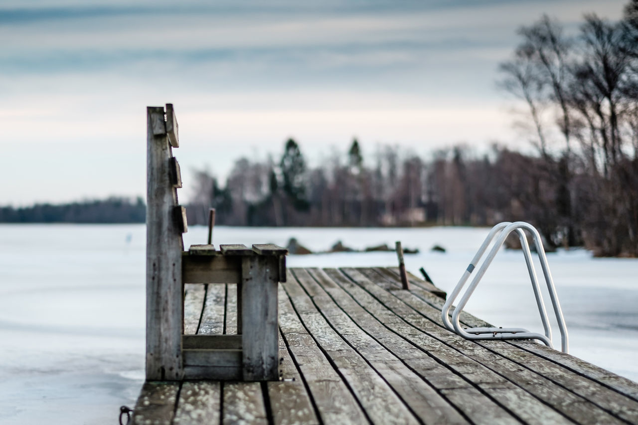 wood - material, winter, pier, focus on foreground, snow, cold temperature, nature, outdoors, no people, water, lake, sky, jetty, day, tree, beauty in nature, scenics, sunset, close-up