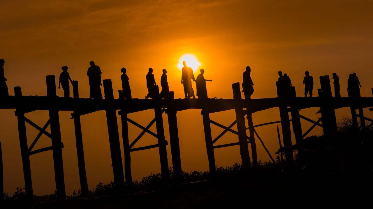 Silhouette People Walking On Bridge Against Sky During Sunset