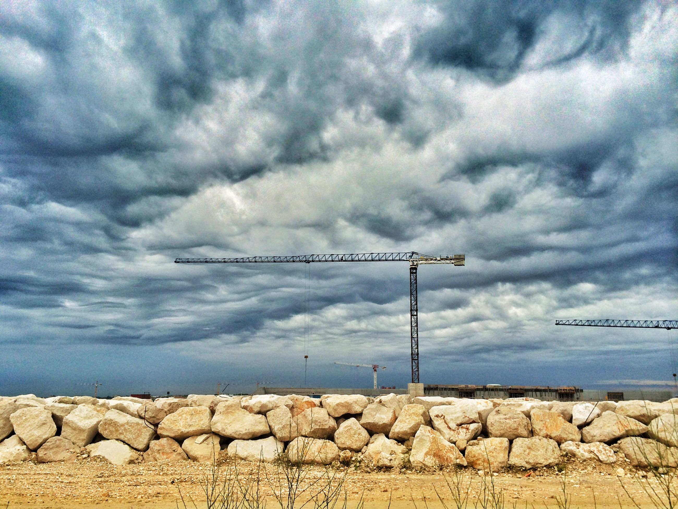 sky, cloud - sky, cloudy, cloud, built structure, sea, fuel and power generation, overcast, architecture, environmental conservation, wind turbine, day, building exterior, alternative energy, low angle view, wind power, nature, outdoors, no people, weather