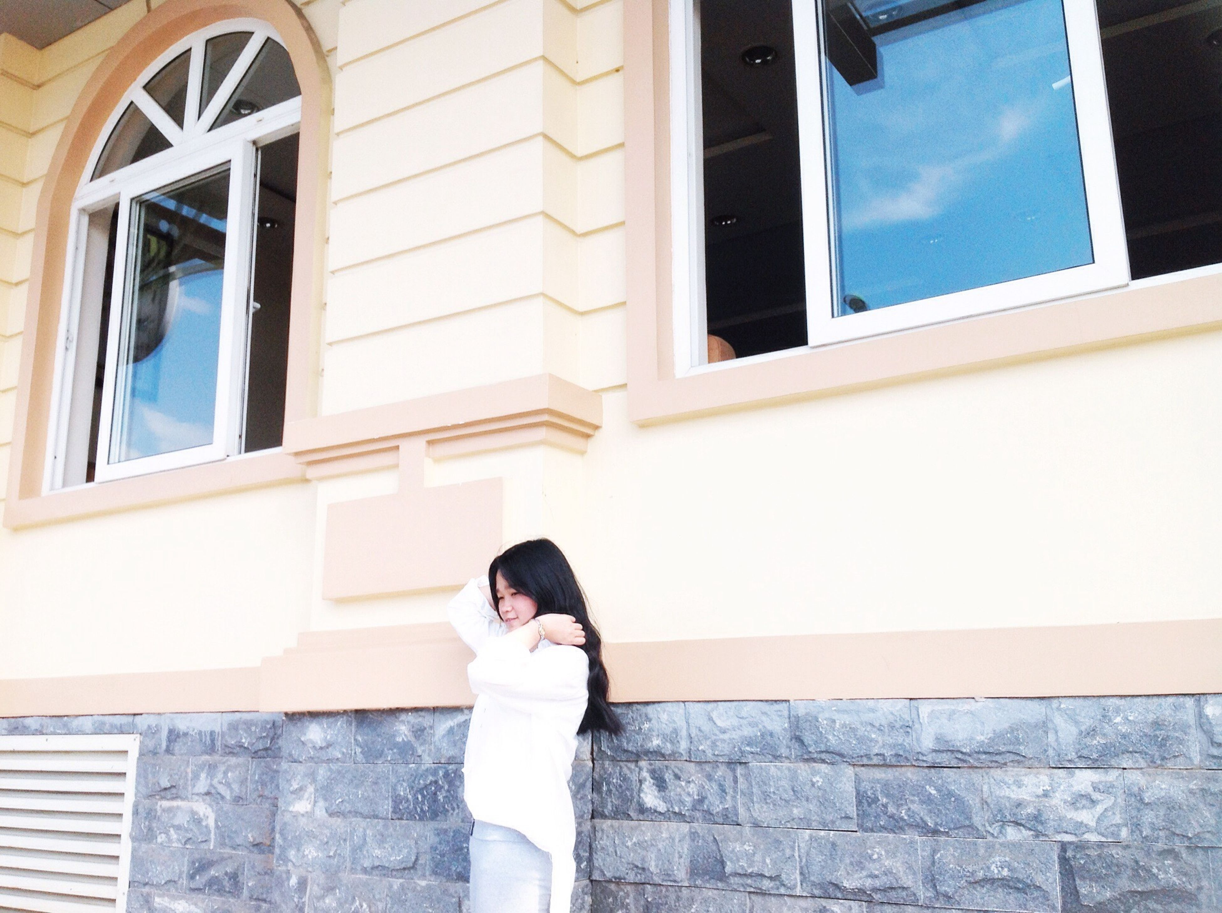 architecture, building exterior, built structure, lifestyles, standing, window, young adult, casual clothing, young women, leisure activity, building, wall - building feature, day, three quarter length, person, waist up, front view, side view