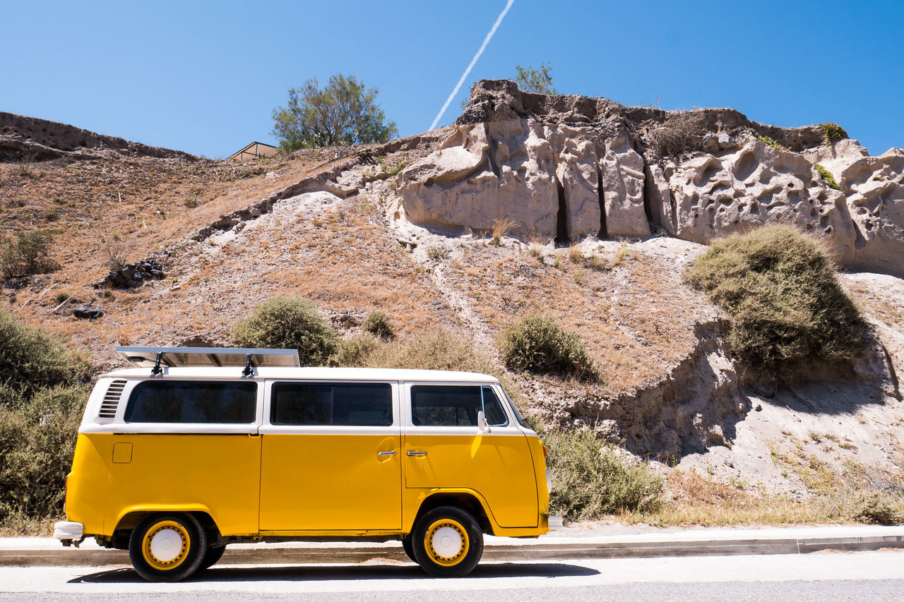 transportation, mode of transport, rock formation, land vehicle, rock - object, outdoors, day, clear sky, mountain, yellow, tree, road, nature, no people, sky