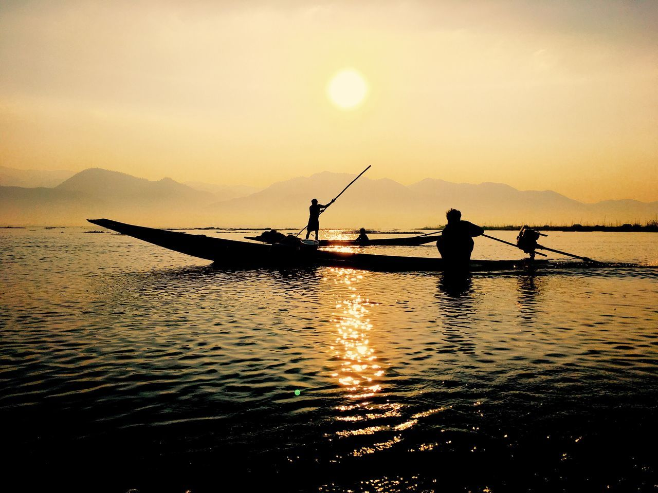 sunset, silhouette, water, nautical vessel, nature, men, transportation, real people, beauty in nature, scenics, sky, oar, one person, outdoors, occupation, rowing, standing, lifestyles, lake, day, people