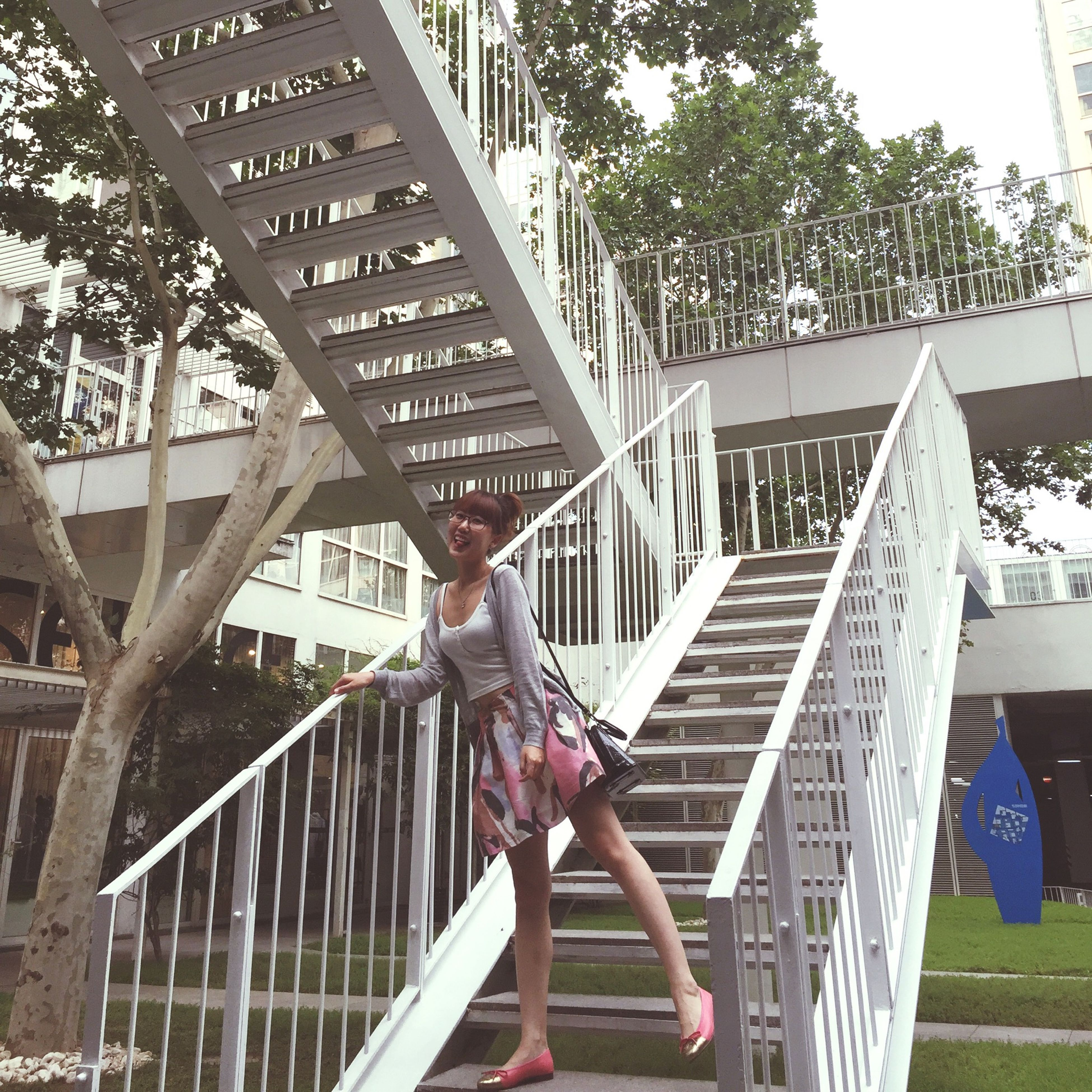 lifestyles, built structure, leisure activity, full length, architecture, railing, casual clothing, person, building exterior, young adult, standing, day, young women, tree, childhood, low angle view, sunlight, outdoors