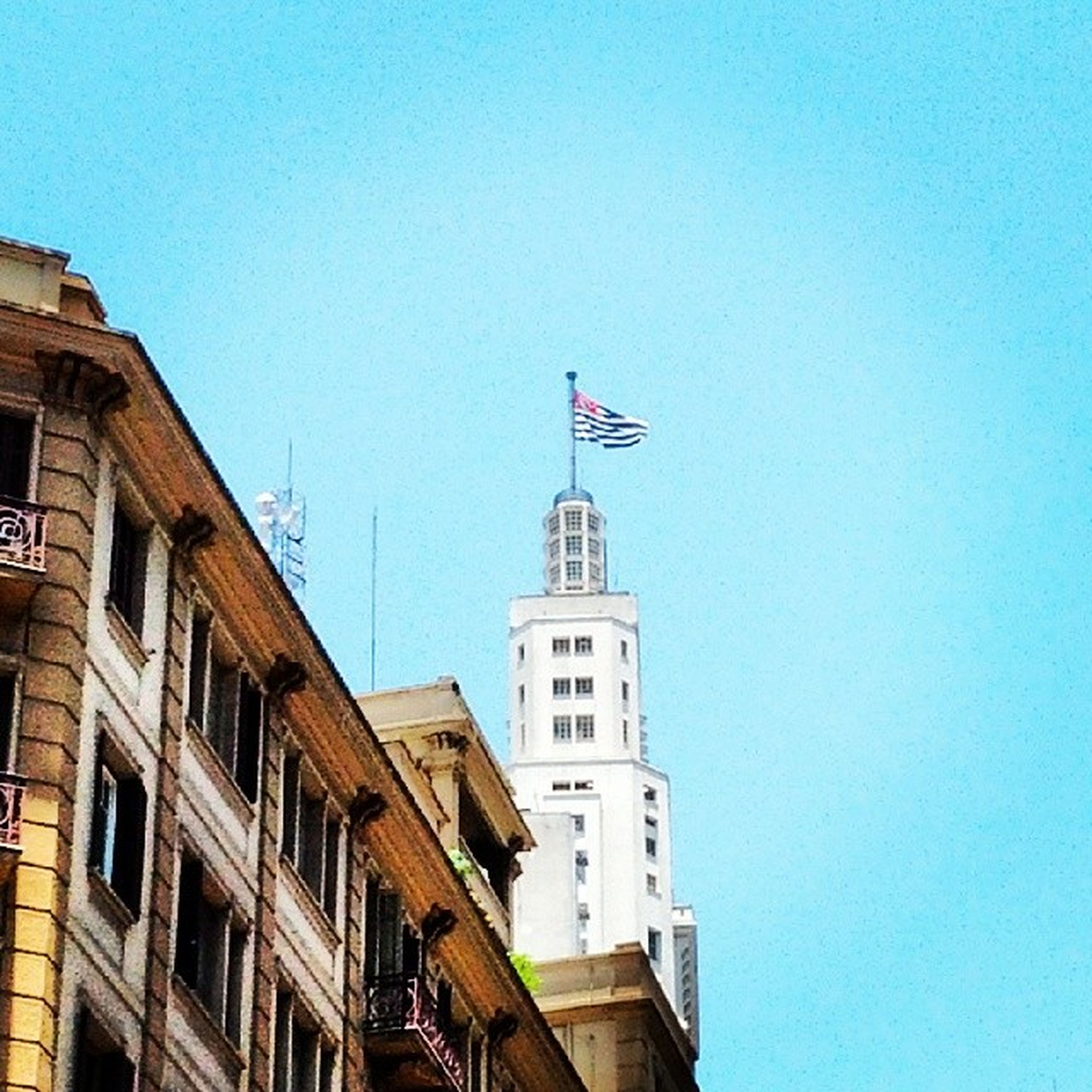building exterior, architecture, built structure, clear sky, low angle view, copy space, blue, flag, city, religion, tower, patriotism, national flag, day, identity, clock tower, high section, outdoors, no people